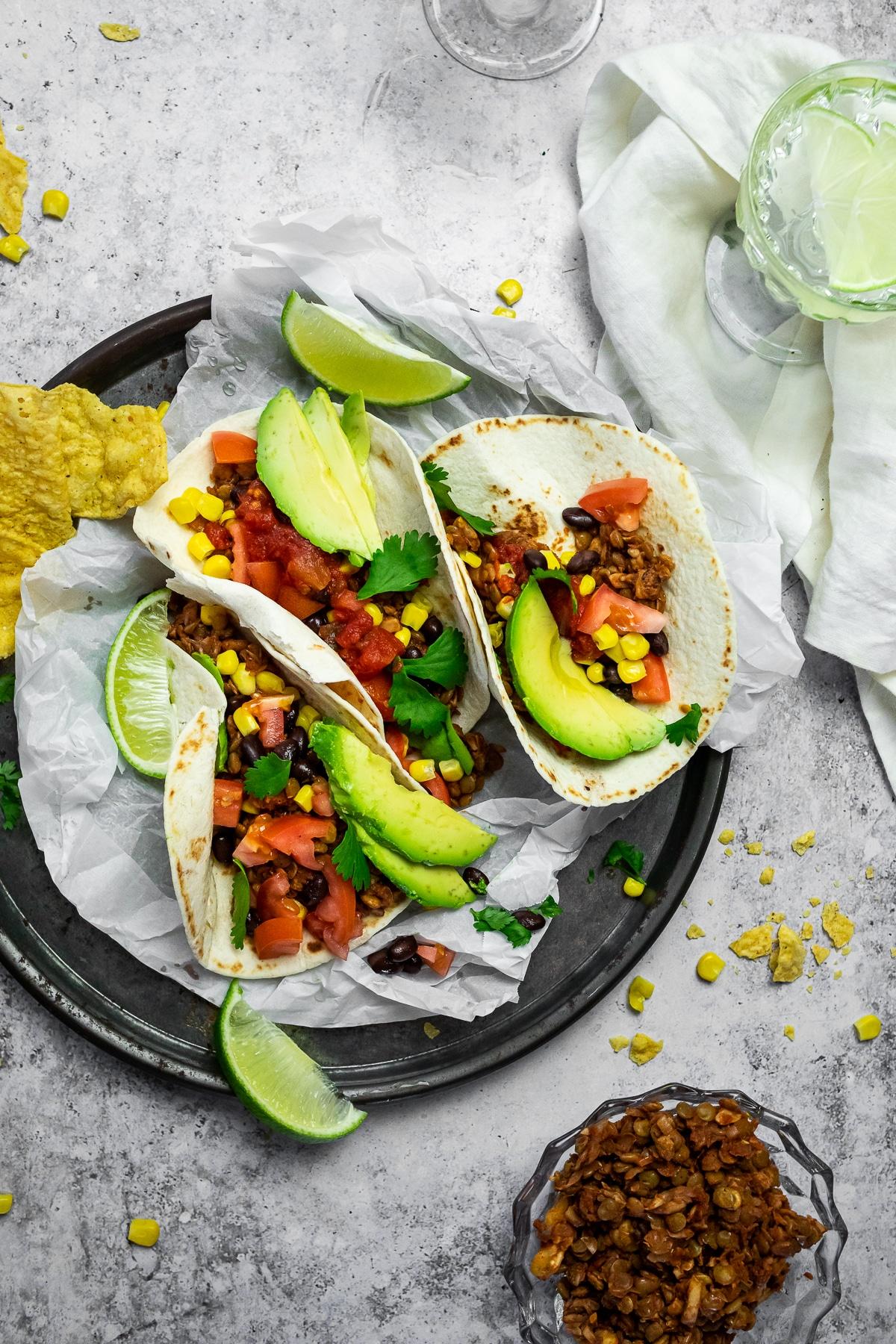 Vogelansicht von 3 Tacos auf einem Servierteller mit einer Schüssel veganem Taco-Fleisch und einer Tasse mit Wasser.