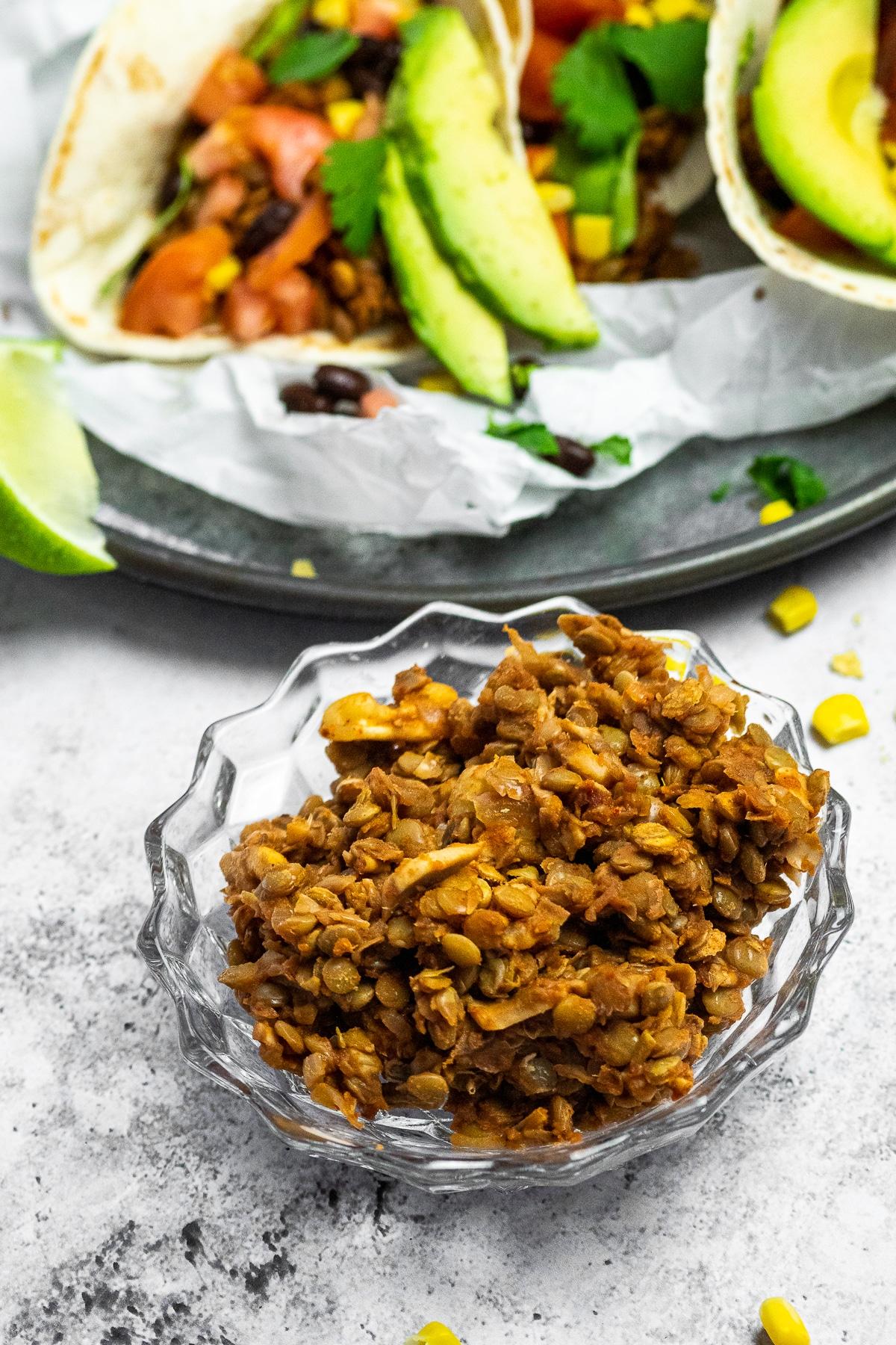 Veganes Taco-Fleisch in einer Schüssel mit Tacos im Hintergrund verschwommen.