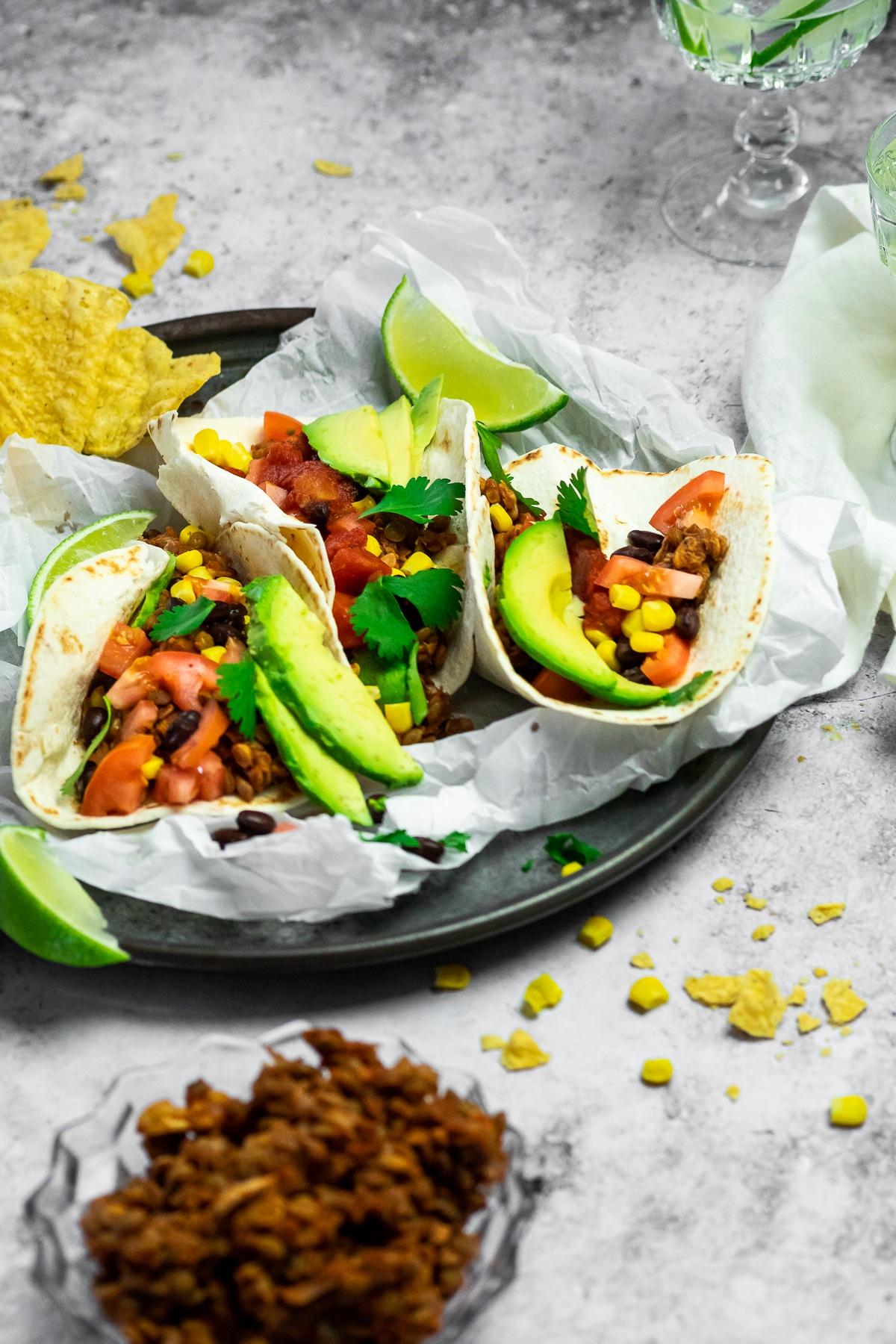 Servierteller mit Pergamentpapier und 3 Tacos darüber und serviert mit Tortillachips