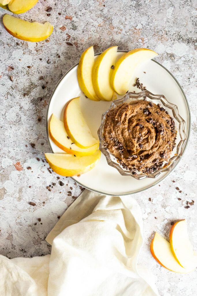Vogelansicht eines Tellers mit geschnittenen Äpfeln und einer Schüssel mit veganem Brownie Teig Hummus