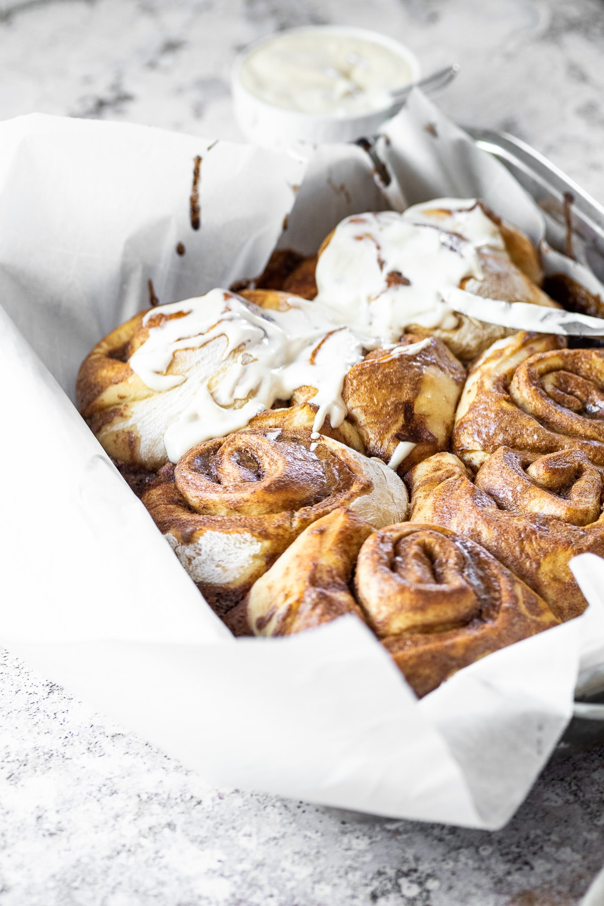 75° ankle of a pan with cinnamon buns and some are topped with icing