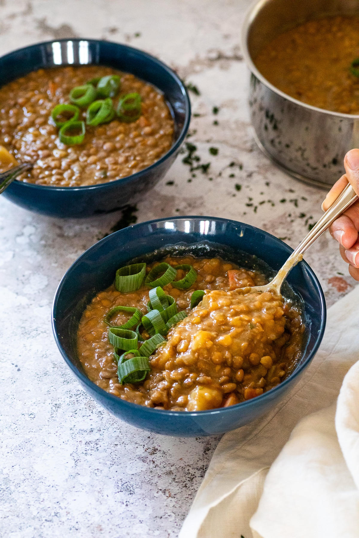 Holding a spoon over a bowl with lentil soup.