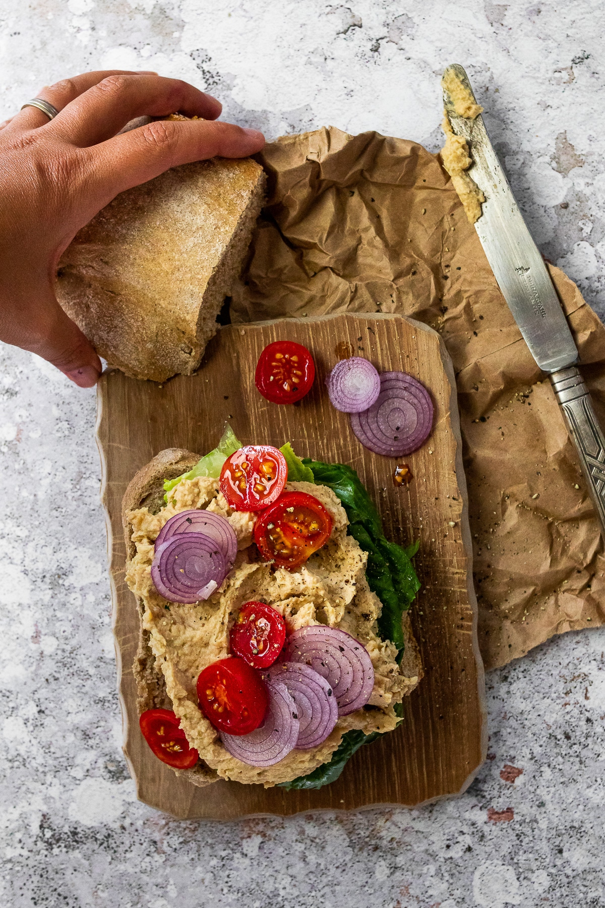 Bird view of an open vegan tuna sandwich laying on a wooden board. With a knive on the side and one bun half above.