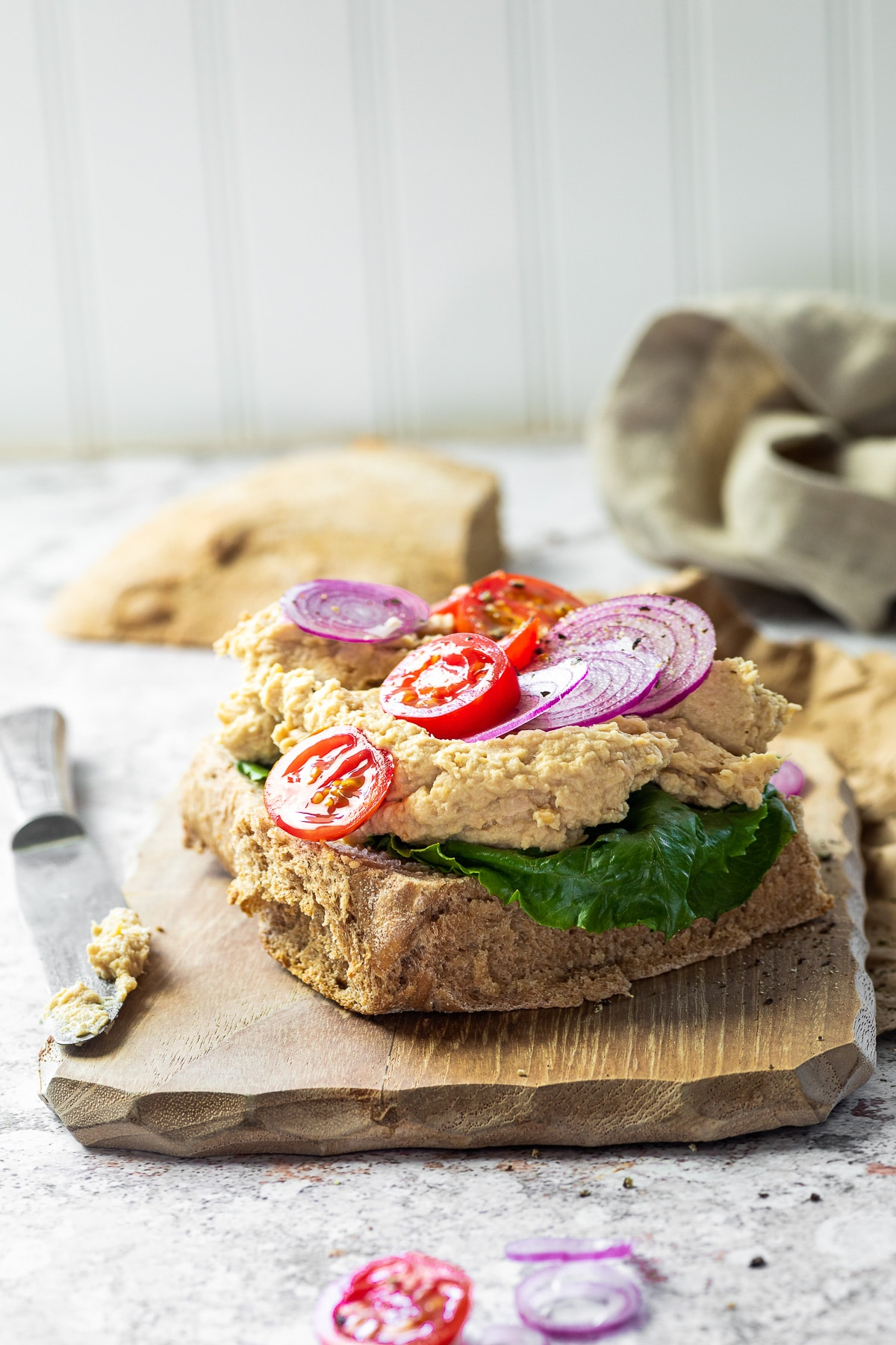 straight view on a vegan tuna sandwich toast topped with tomatoes and onions