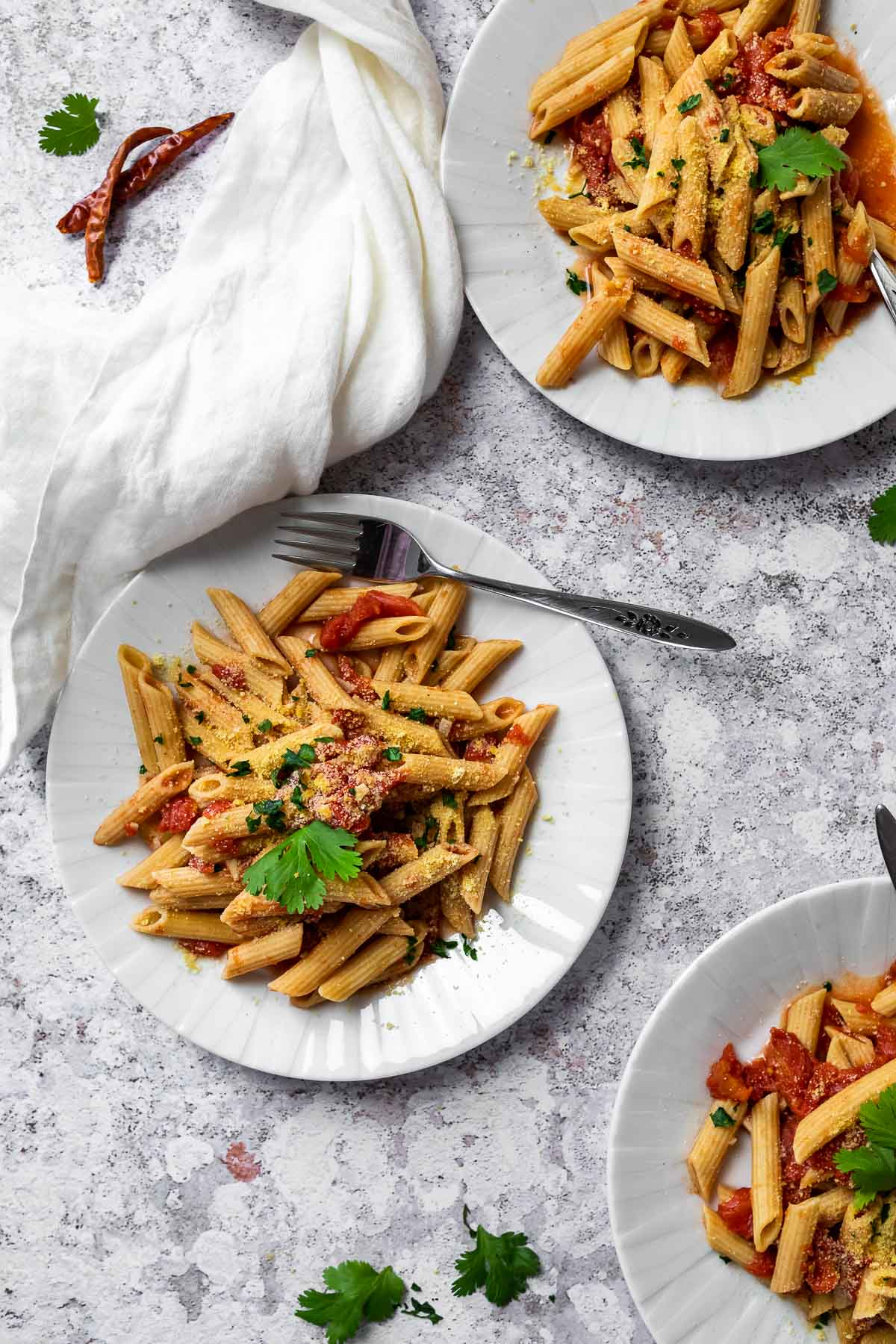 Three plates loaded with penne all arrabiata.