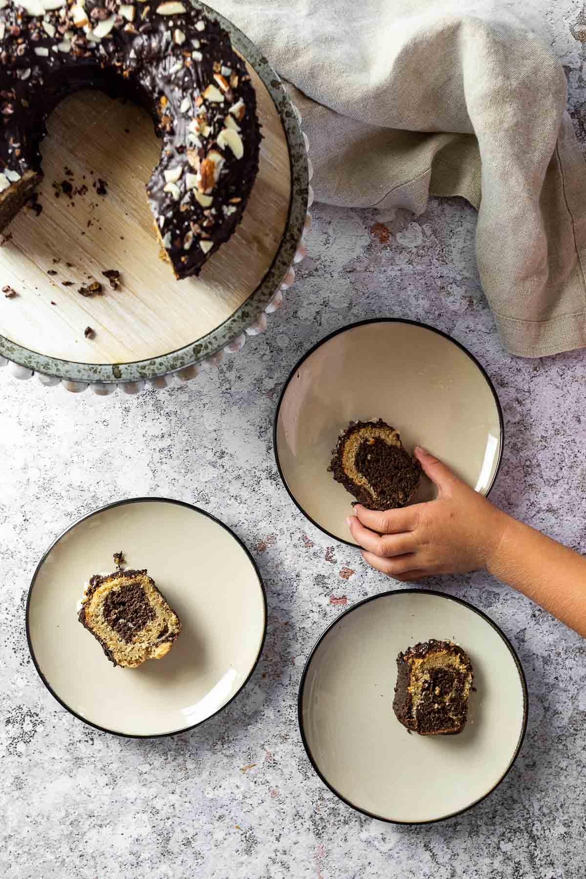 3 Teller mit je einem Stück Marmorkuchen und der Kuchenständer mit dem Kuchen darüber. Ein Stück halten.