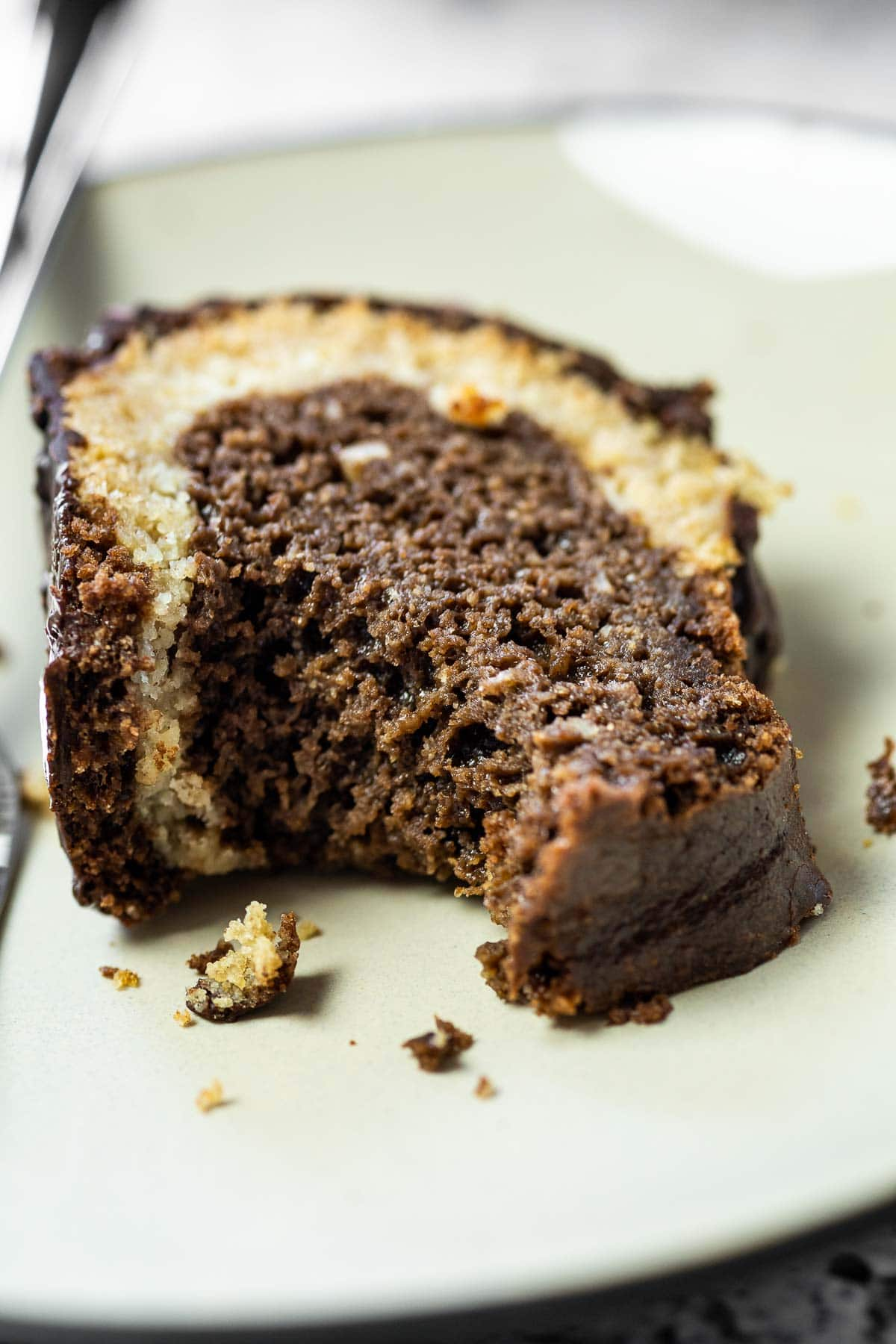 A piece of vegan marble cake on a plate with a bite missing