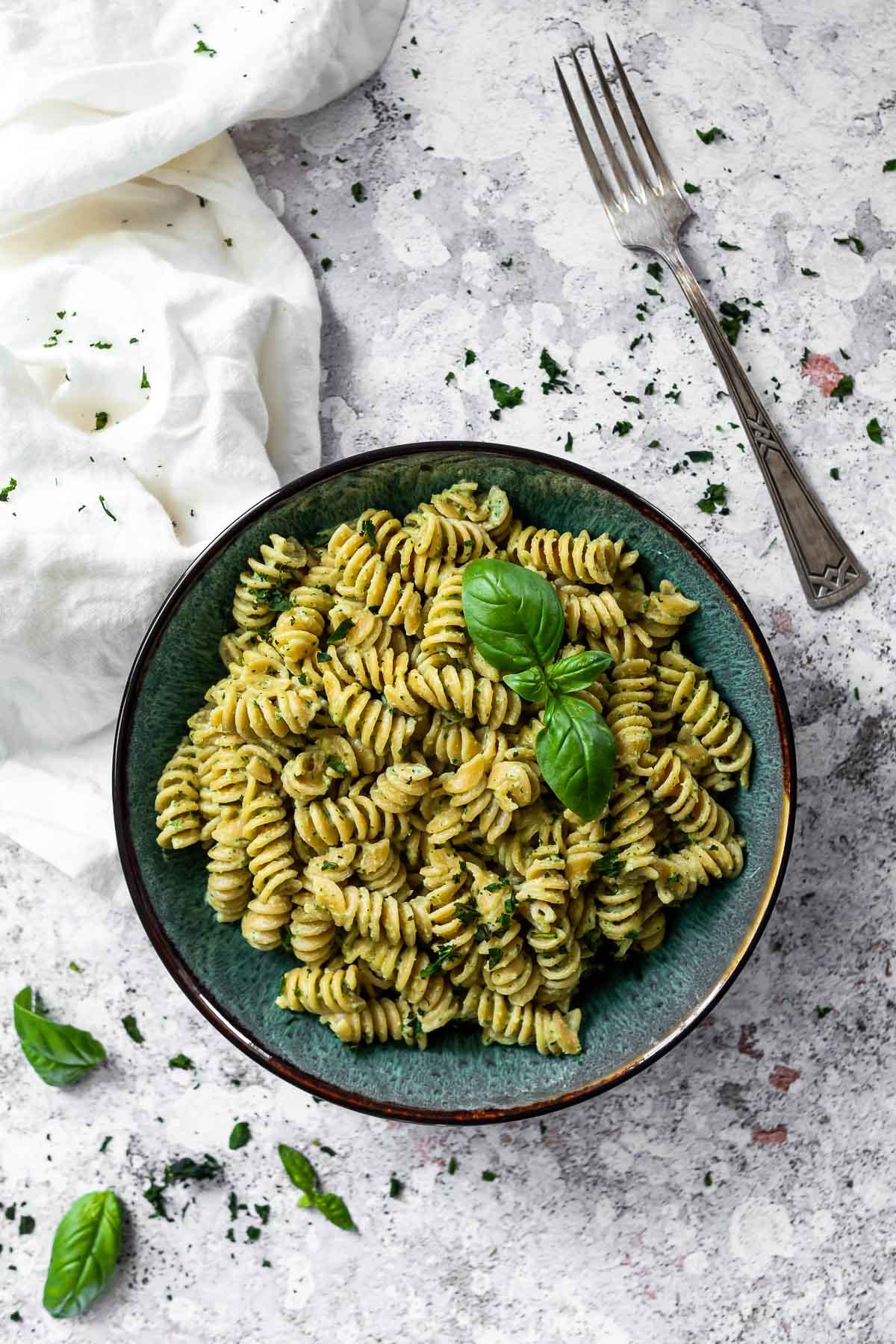 Bowl with vegan pasta dressed in a vegan basil cream sauce.