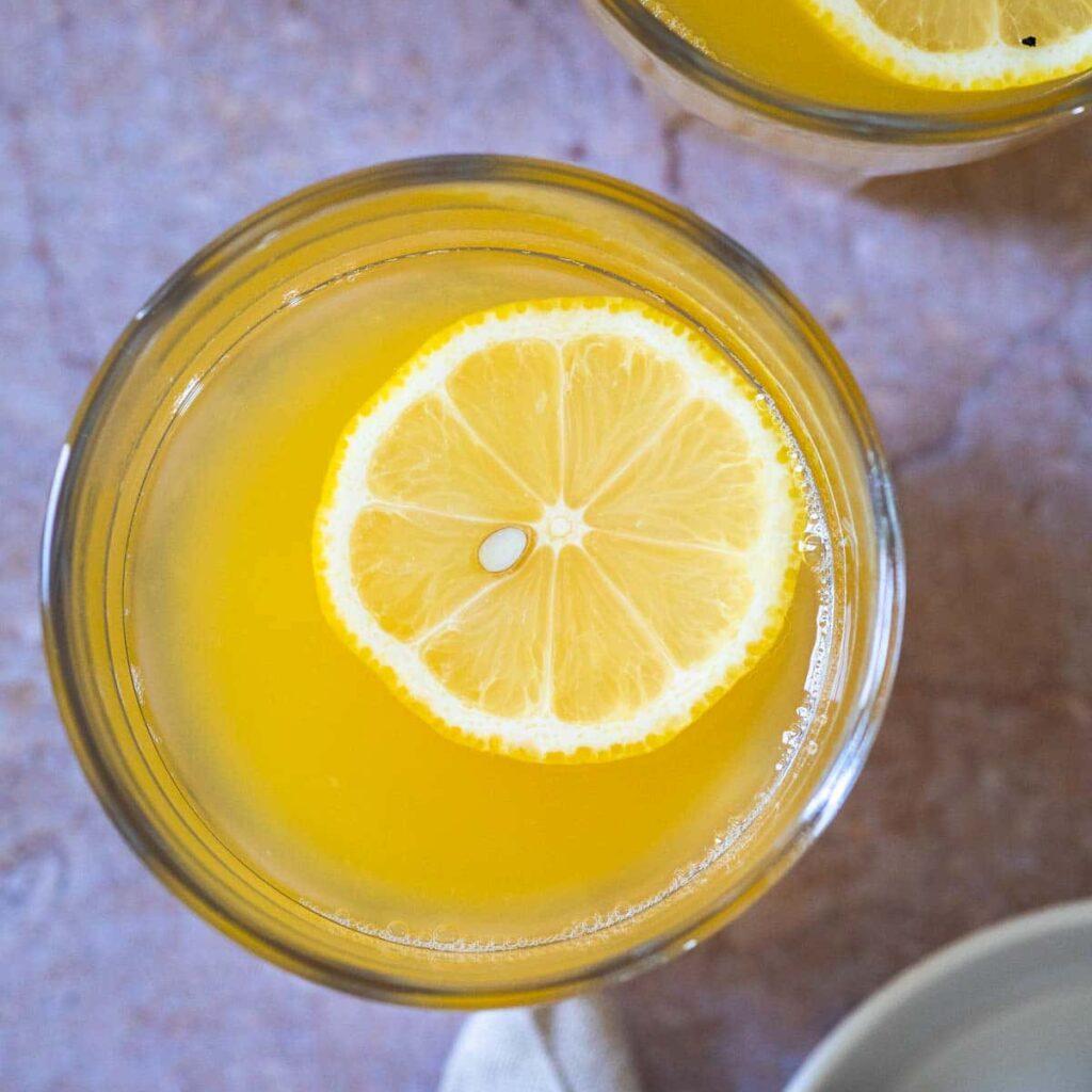 Vogelansicht einer Tasse mit warmer Limonade mit einer schwimmenden Zitronenscheibe.