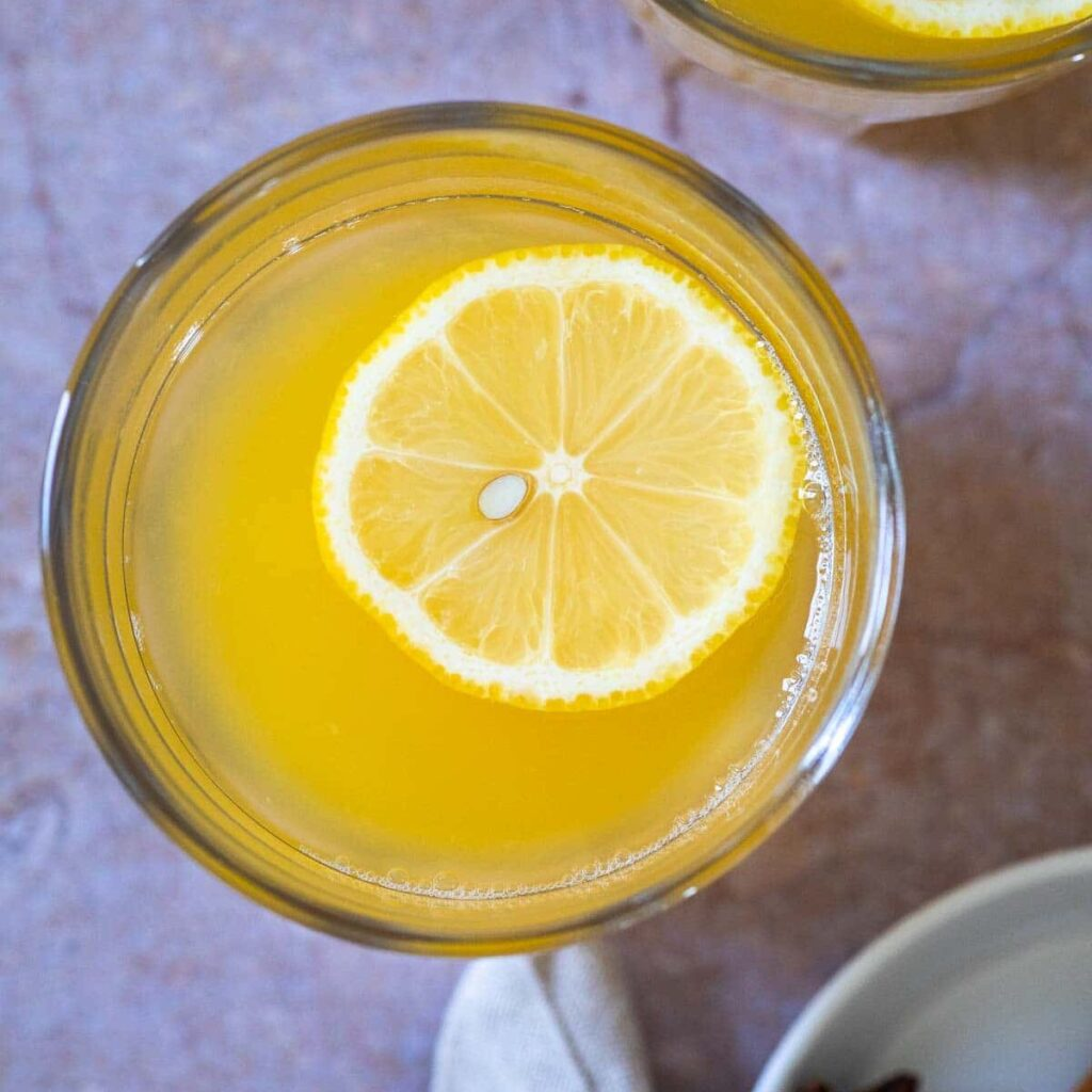 Bird view of a cup with warm lemonade with a slice of lemon floating.
