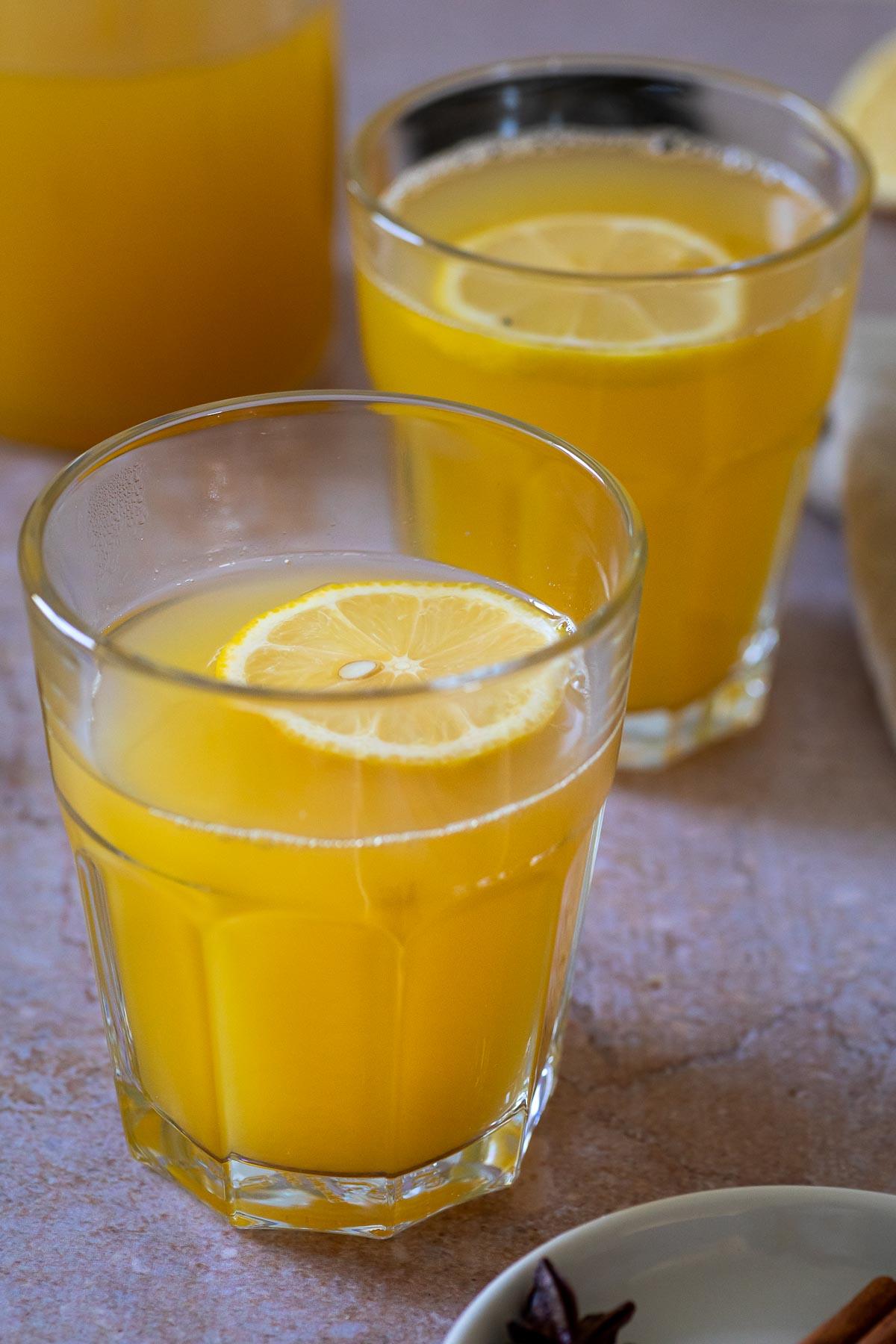 2 Gläser mit warmer Winterlimonade mit einer Zitronenscheibe darüber.