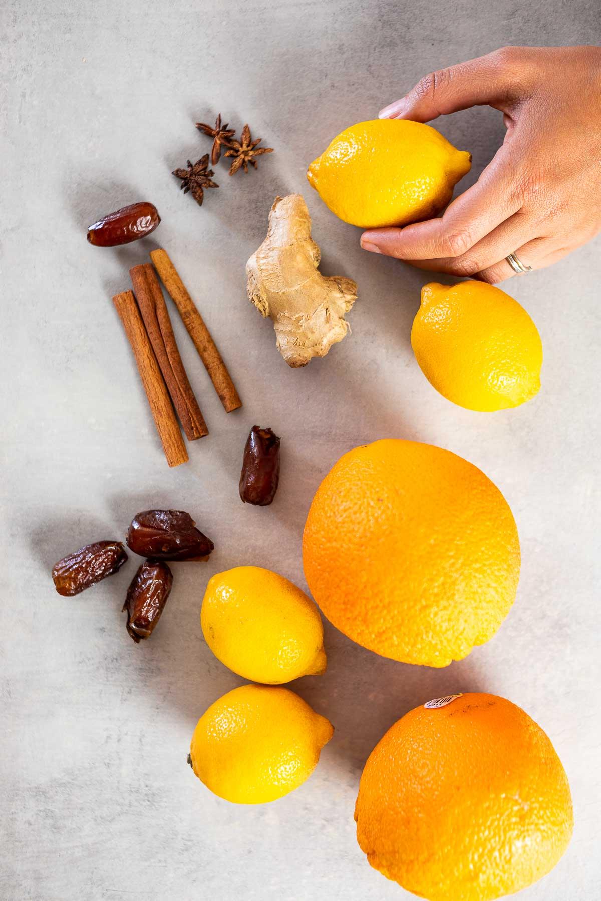 Ingredients shot of the winter lemonade: Anise, cinnamon sticks, dates, lemon, oranges, ginger