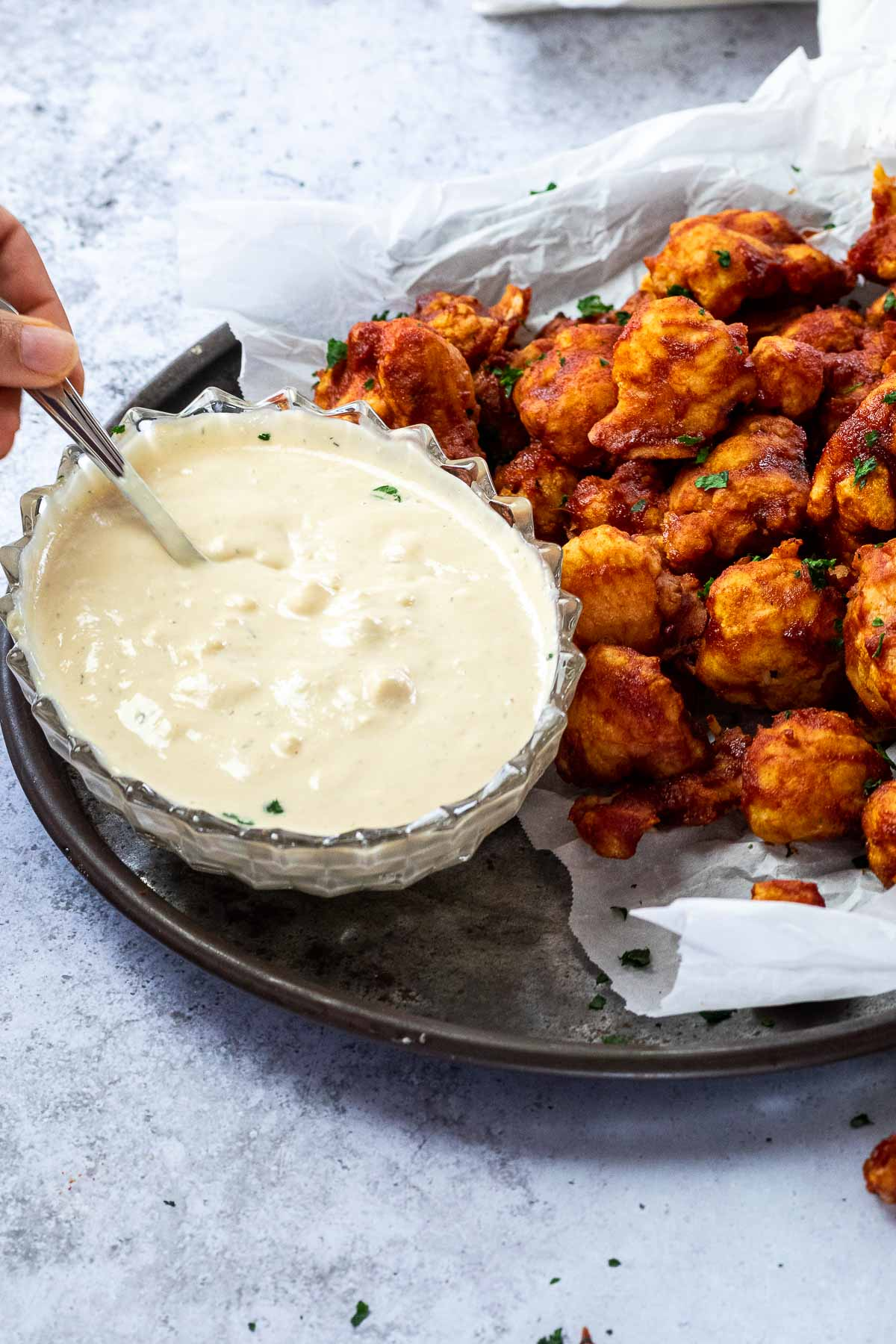 Bowl of vegan blue cheesedressing with a spoon served on a platter with bbq wings