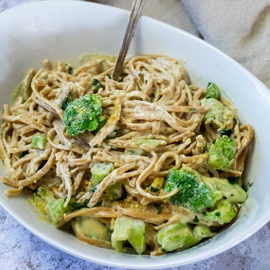 Dairy free Alfredo Sauce with spaghetti and broccoli served in bowl with a fork