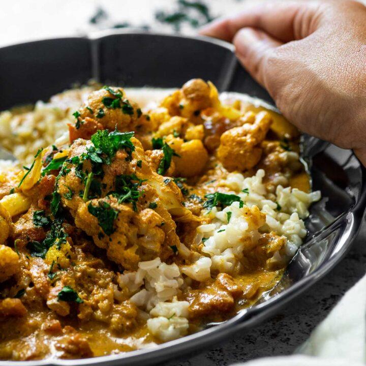 Halten Sie die Schüssel mit veganem Butterhuhn mit Reis. Nahansicht