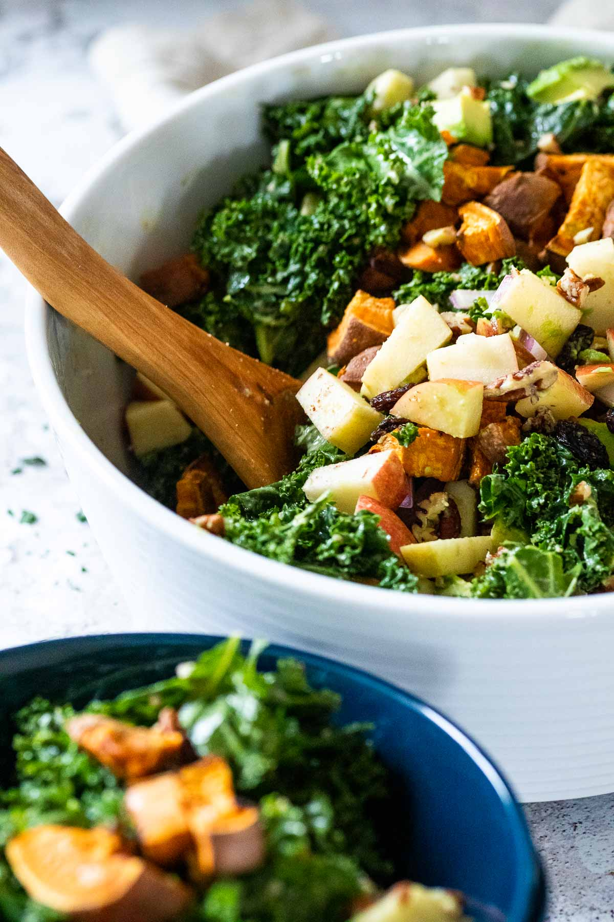 In focus one big bowl of kale salad with a blurred blue bowl in front