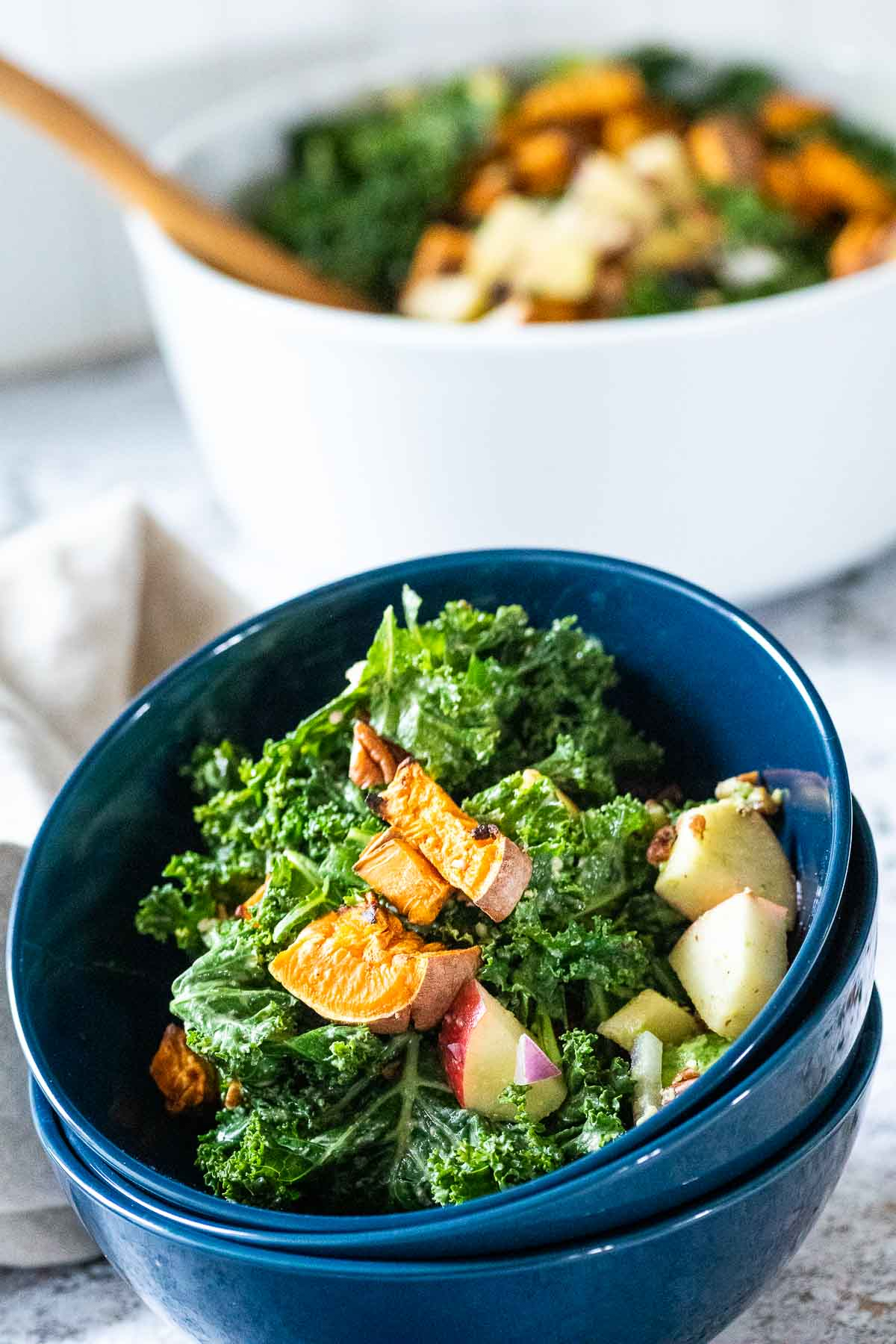 Staple of 3 blue bowls with kale salad on top with blurred big white bowl in the back