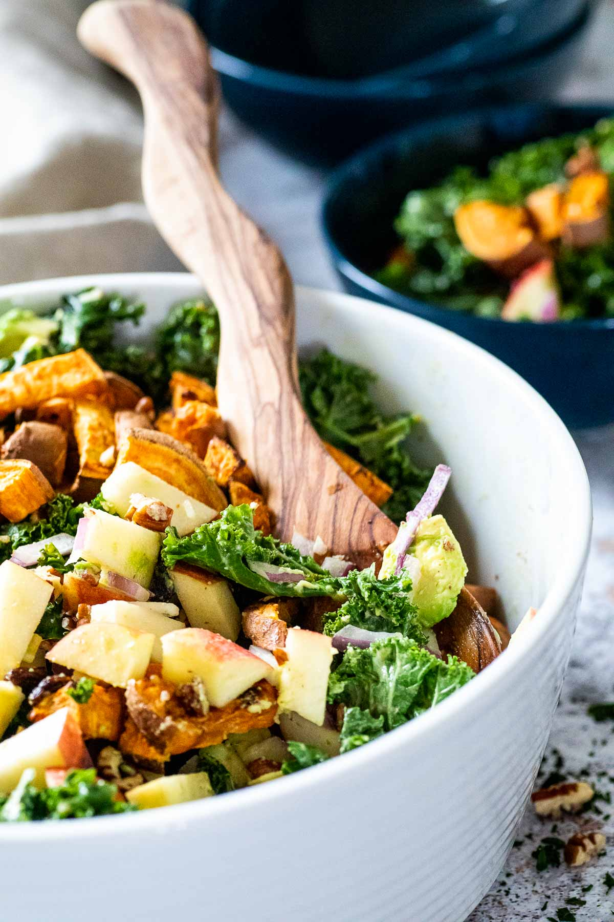 White bowl of kale salad with a serving spoon