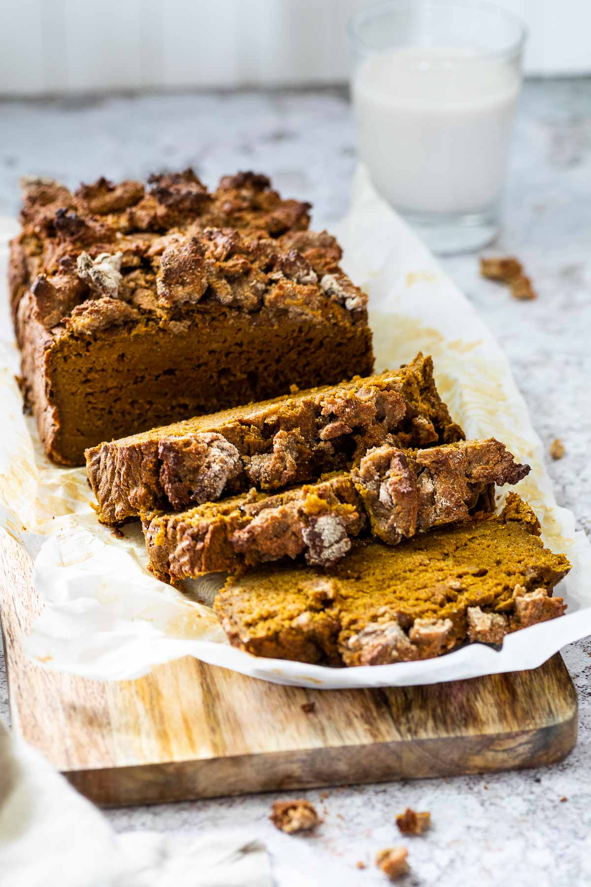 Vegan Pumpkin Bread served on a wooden board with 3 slices.