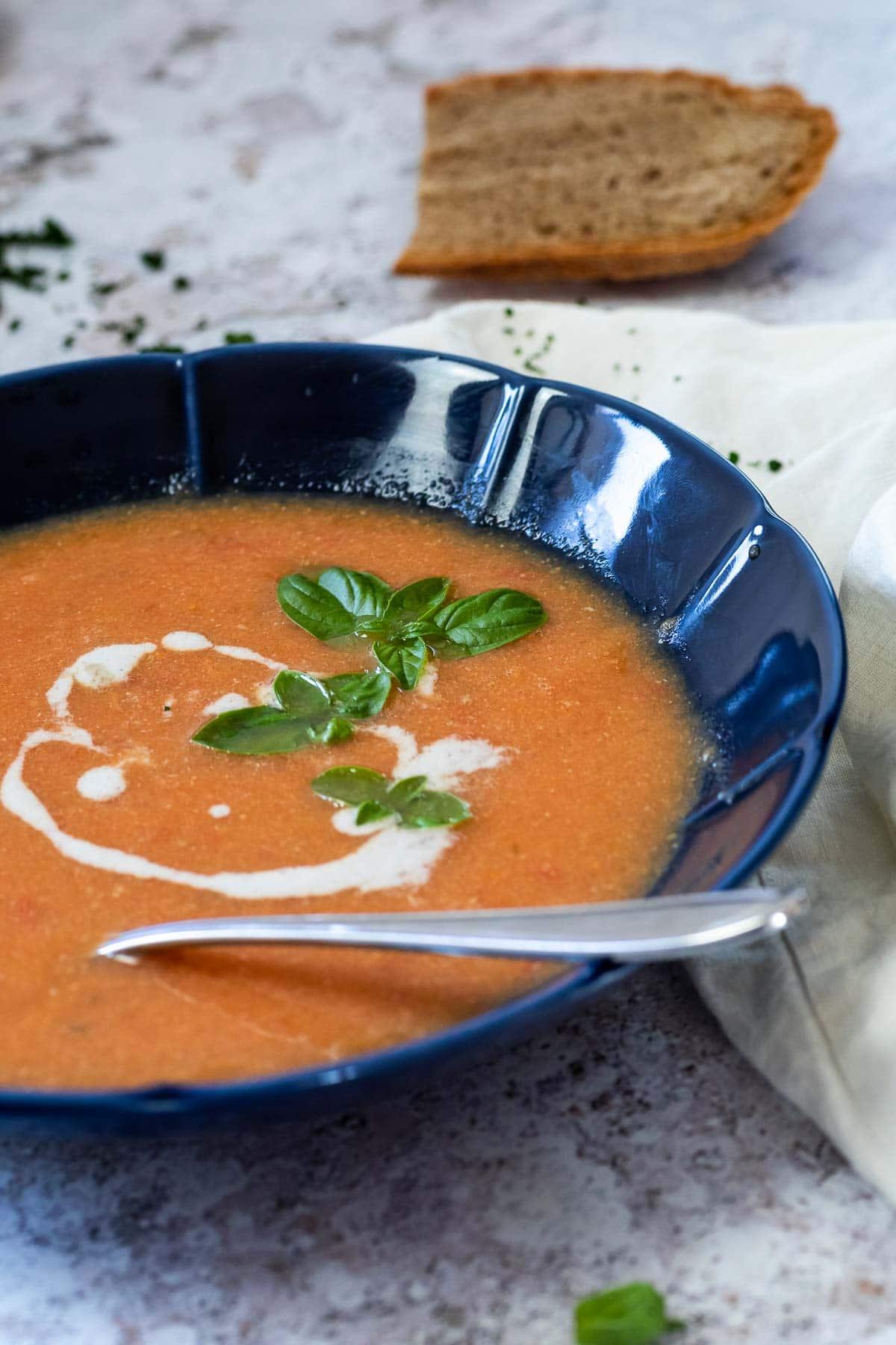 Vegane Tomatensuppe serviert in einer blauen Schüssel mit einem Löffel in der Schüssel. Das Brot liegt verschwommen im Rücken.