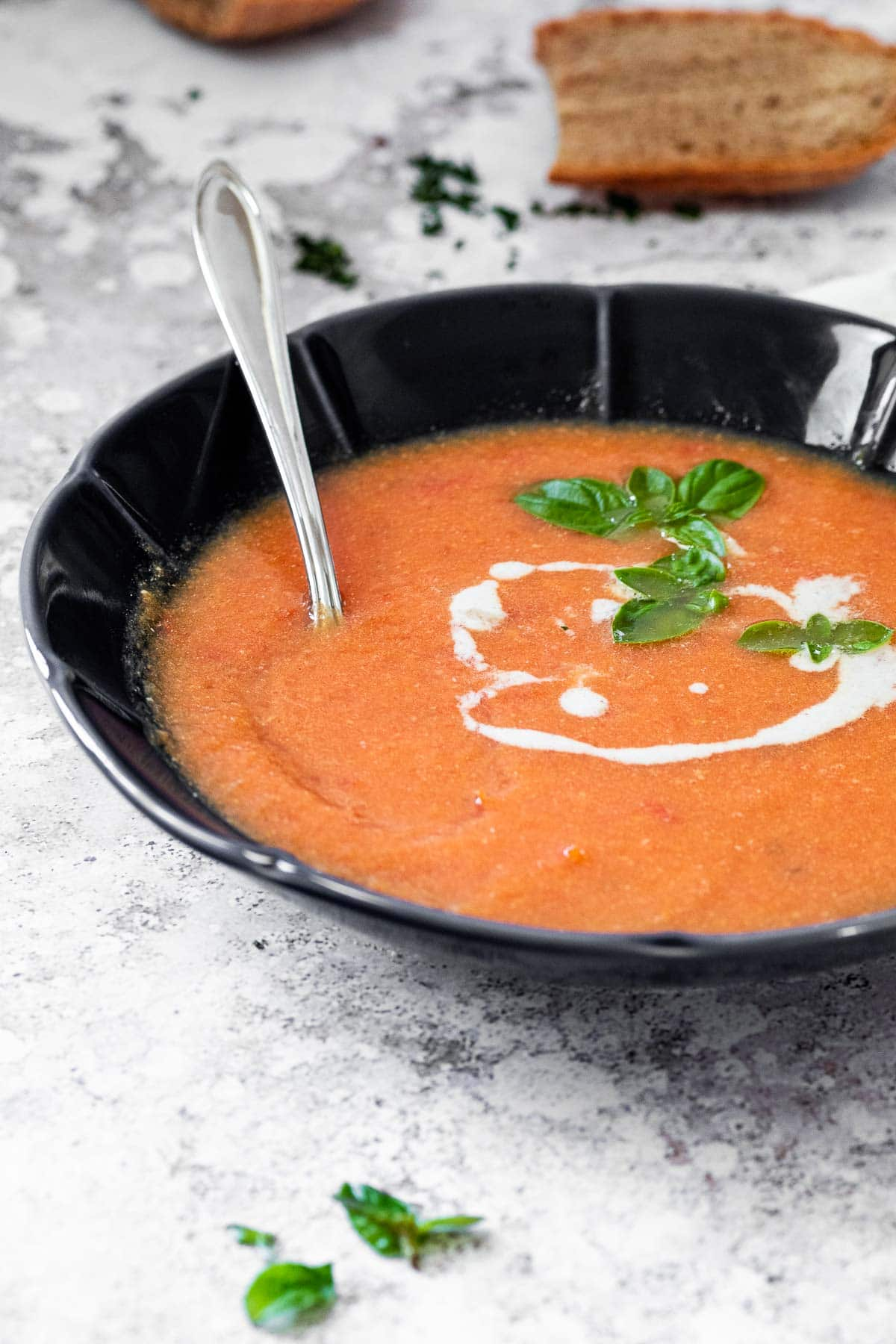 Schwarze Schüssel mit milchfreier Tomatensuppe und einem Löffel zum Essen.