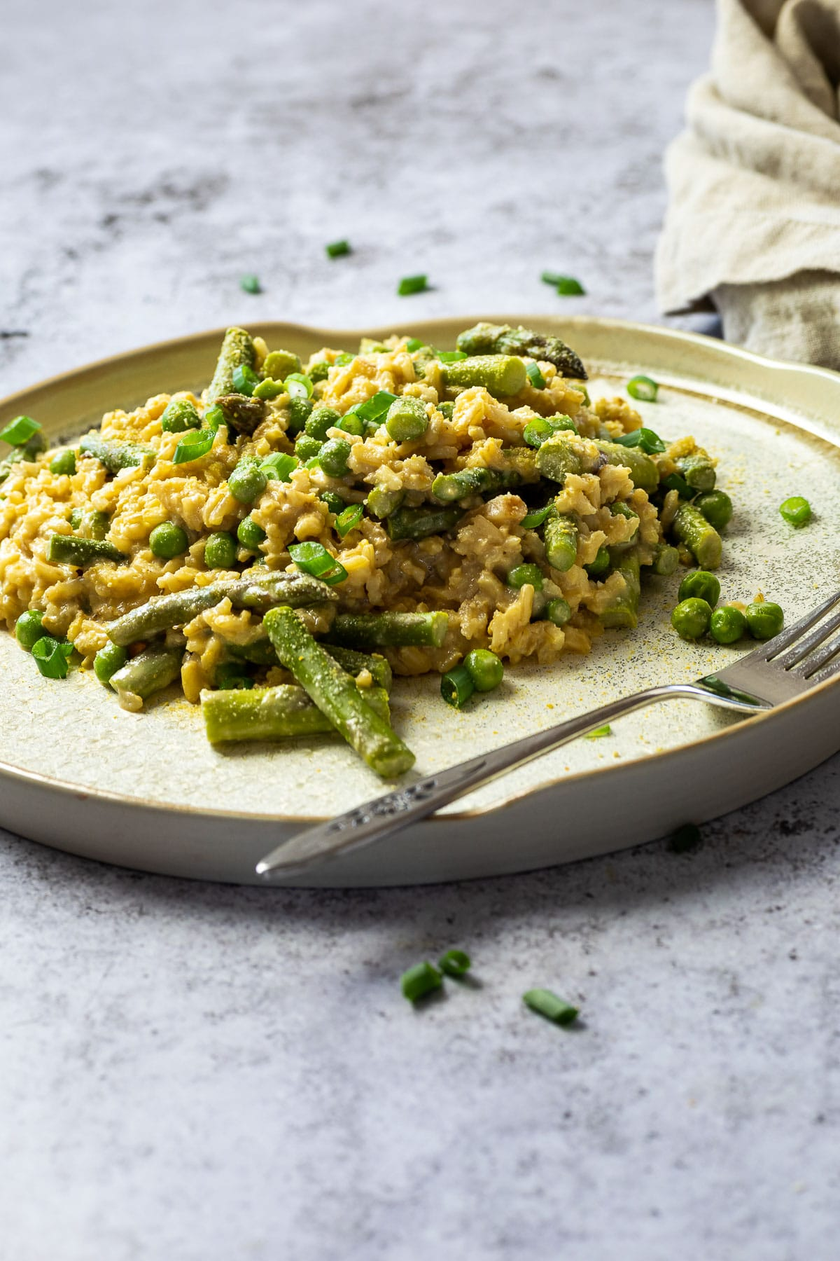 A different ancle of plant based pea and asparagus risotto with a cloth in the background.