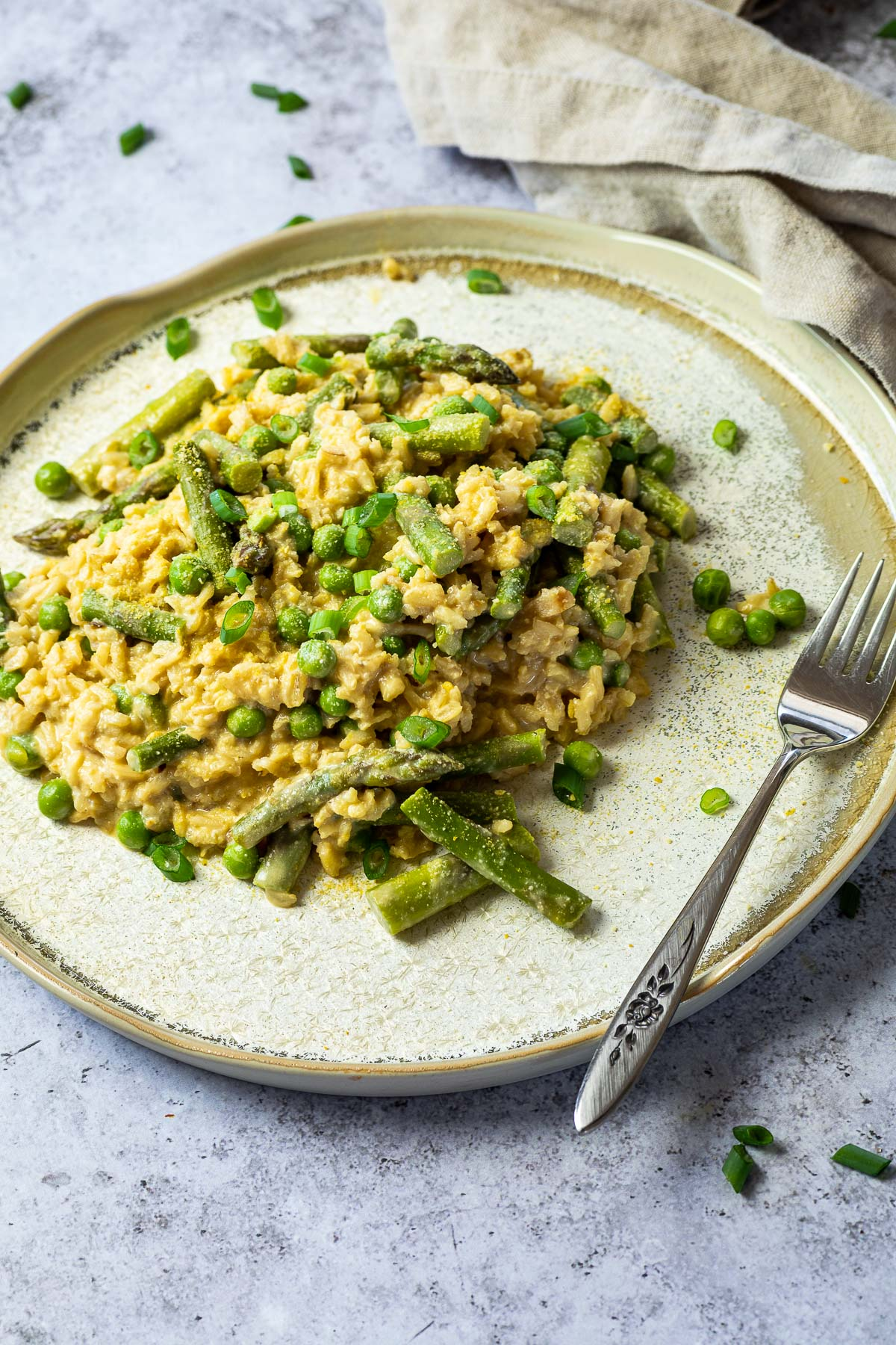 Vegan Pea and Asparagus Risotto on a plate with a fork next to it.