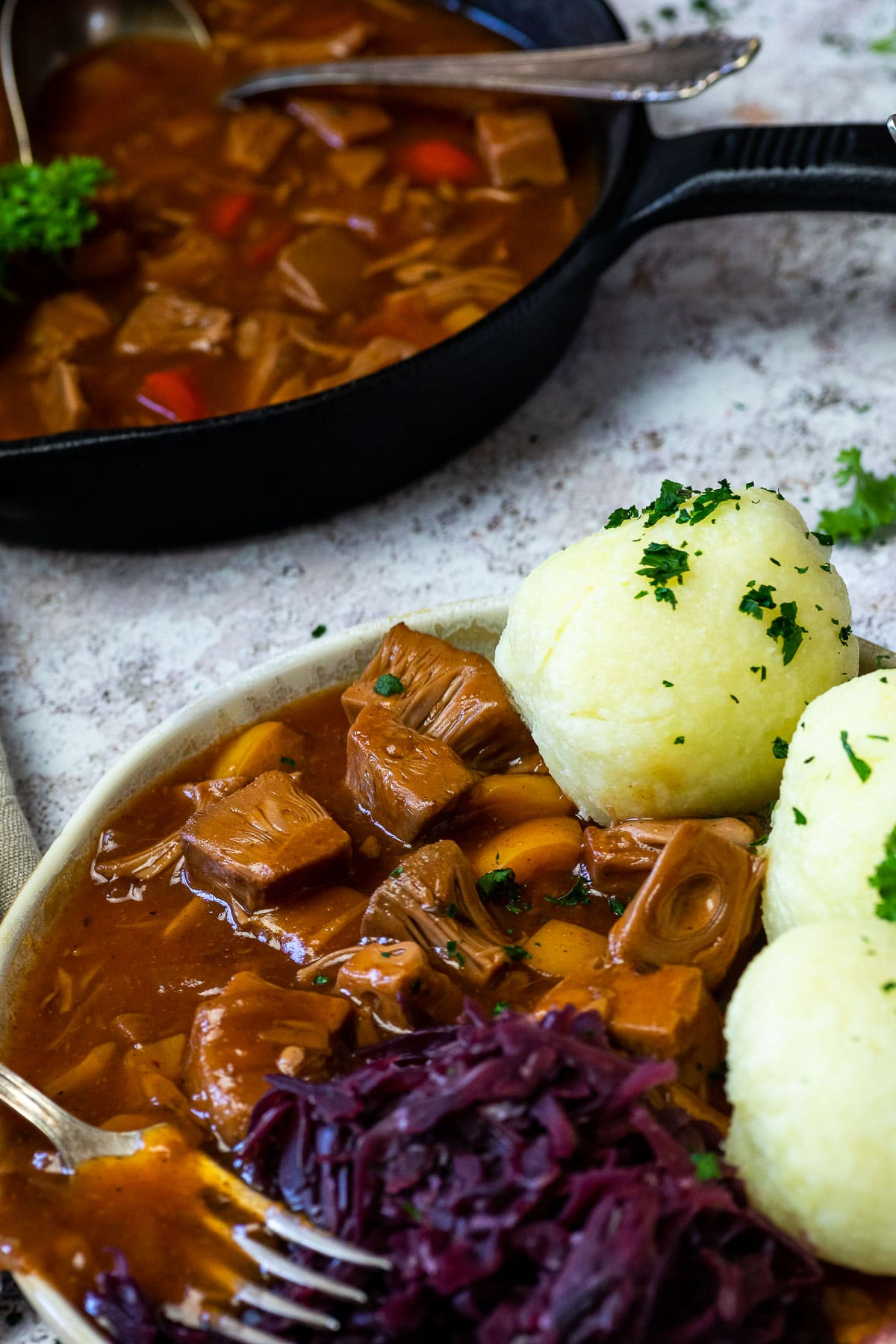 Nahaufnahme des veganen ungarischen Gulasches, das auf einem Teller mit Knödeln und Rotkohl serviert wird. Hinten eine gusseiserne Pfanne.