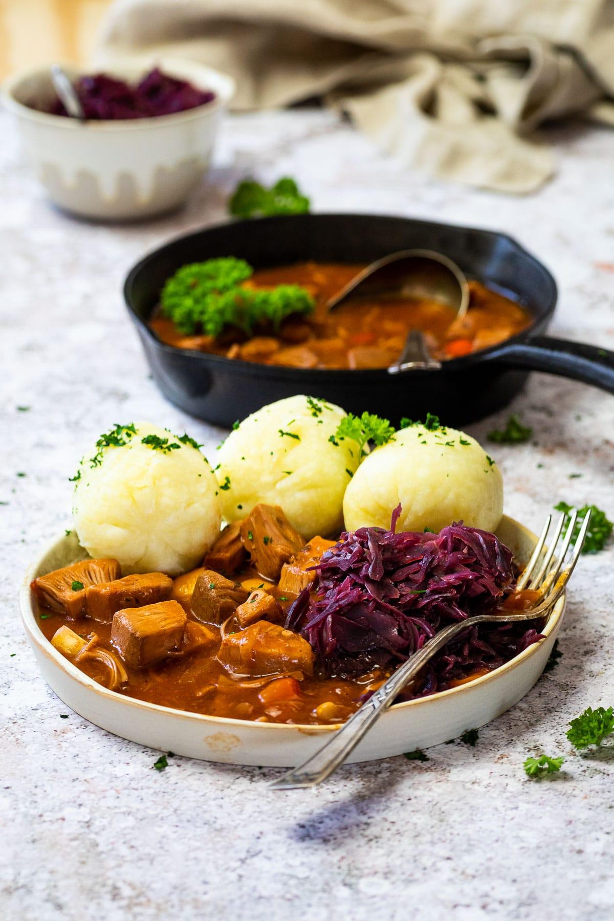 Eine Pfanne und ein Teller mit ungarischem Gulasch auf pflanzlicher Basis
