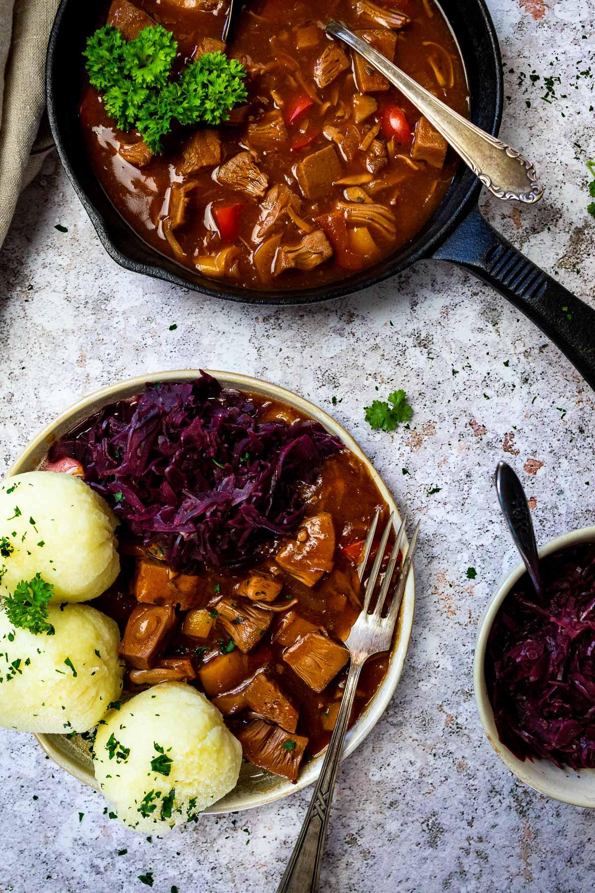 Veganes ungarisches Gulasch serviert mit Kartoffelknödeln und sautiertem Rotkohl und ungarischem Gulasch in einer gusseisernen Pfanne.