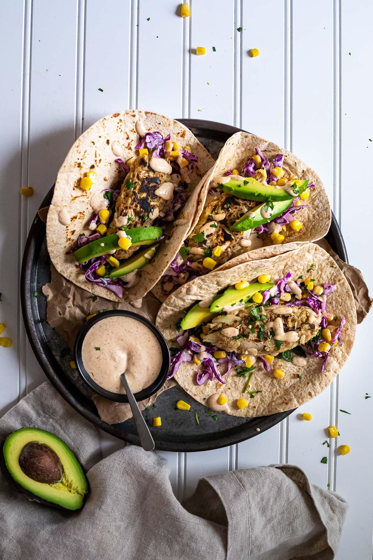 Bird View of a platter with 3 vegan fish tacos and a mini sauce bowl.