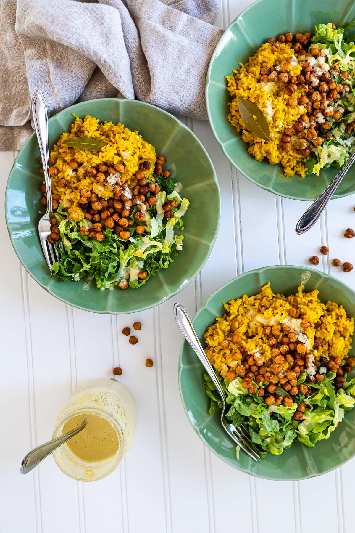 Bird view of three bowls of turmeric rice, lettuce, chickpeas and sauce.