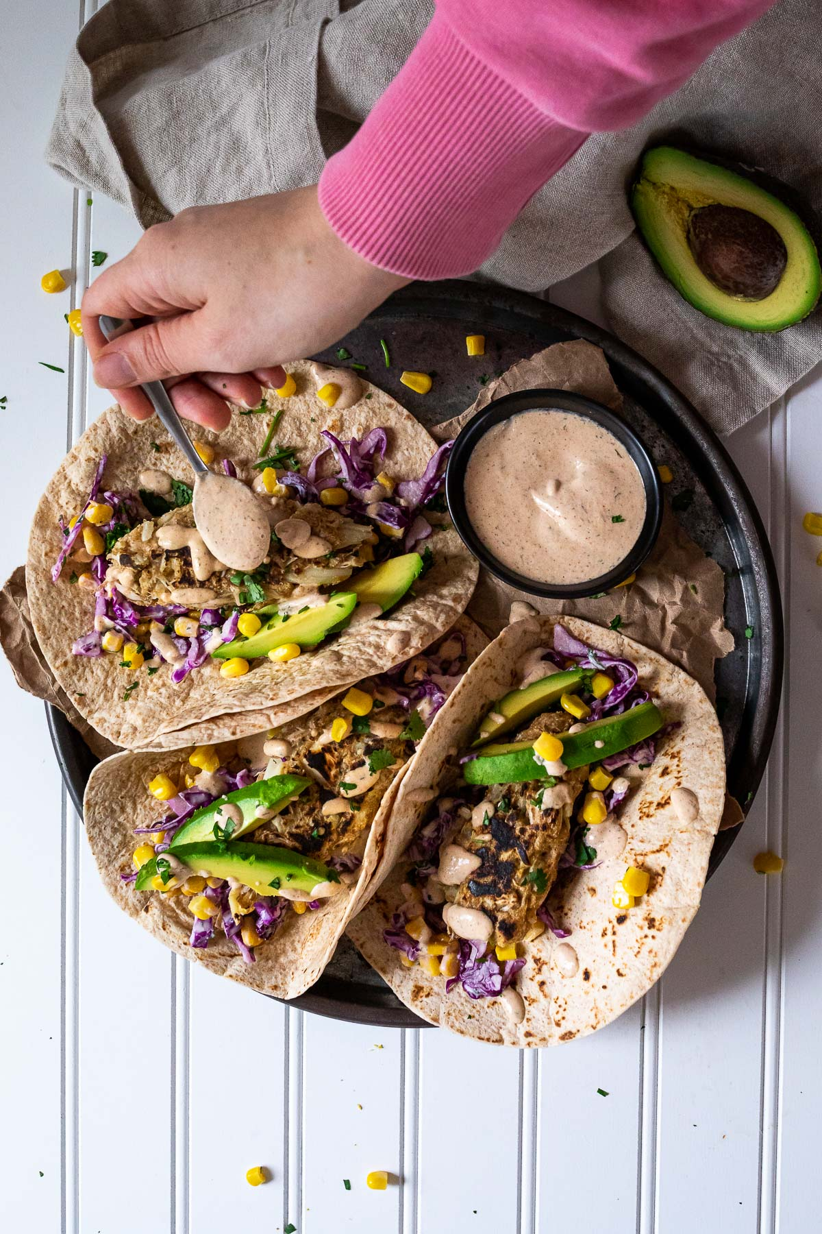 Vegan Fish Taco Platter with Sauce. Pouring some sauce over one of the tacos.