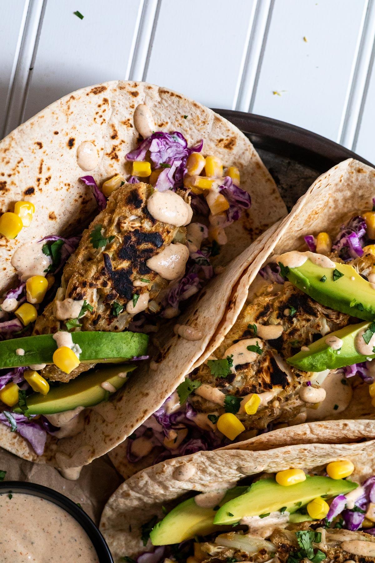 Vegane Fisch-Tacos werden auf einer Platte mit einer Min-Schüssel mit Sauce und einer halben Avocado im Rücken serviert.
