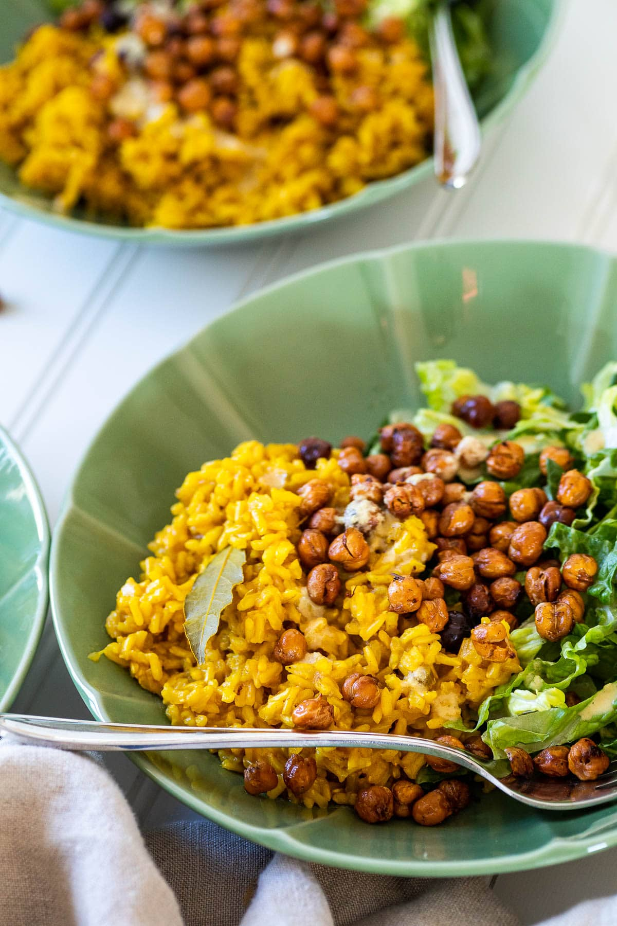 A bowl with turmeric rice, lettuce and crispy chickpeas in front of another bowl.