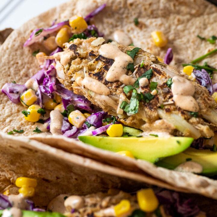 Ein veganer Fischstäbchen im Fokus wird in einem veganen Taco serviert.