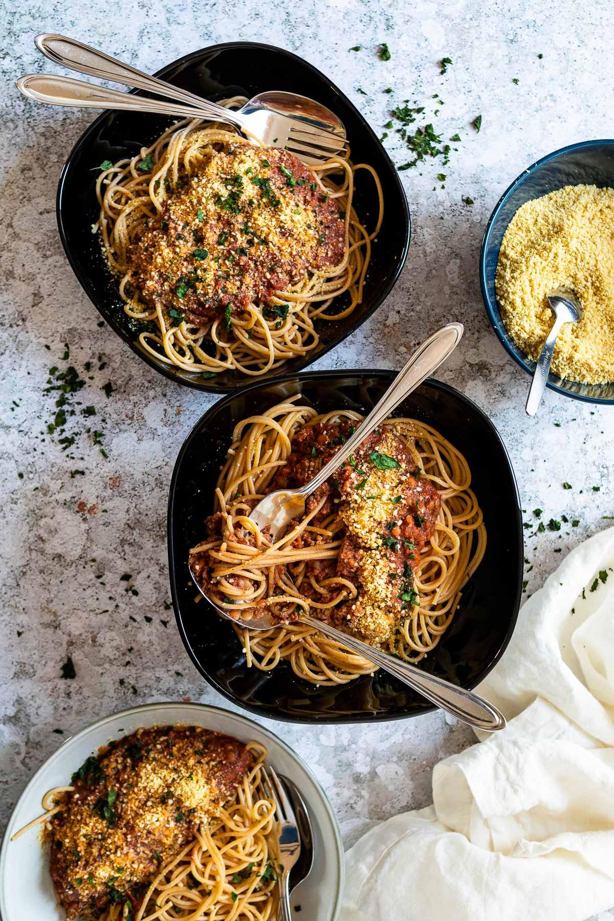 3 Nudelschalen mit Spaghetti und veganer Bolognese-Sauce mit etwas veganem Parmesan