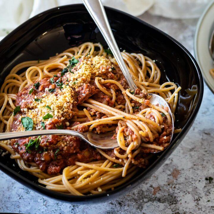 Eine Schüssel mit veganem Bolognese und Spaghetti im Fokus