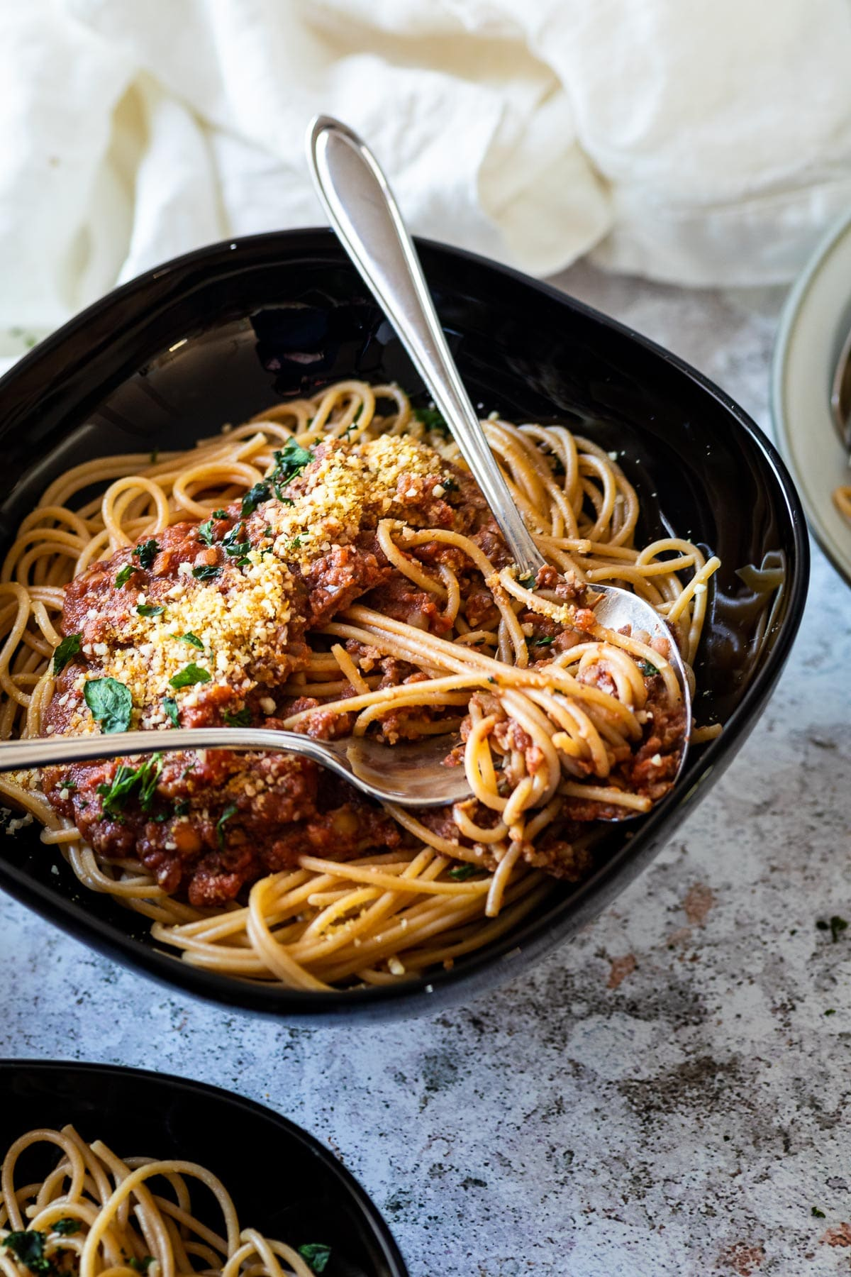 A bowl with vegan bolognese and spaghetti in focus
