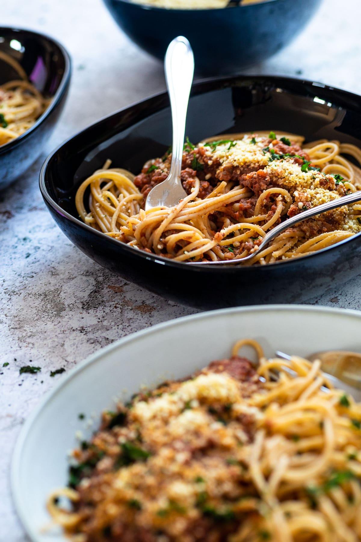Hinten eine Spaghetti-Schüssel mit veganem Bolognese im Fokus. Andere Schüssel vor ist verschwommen