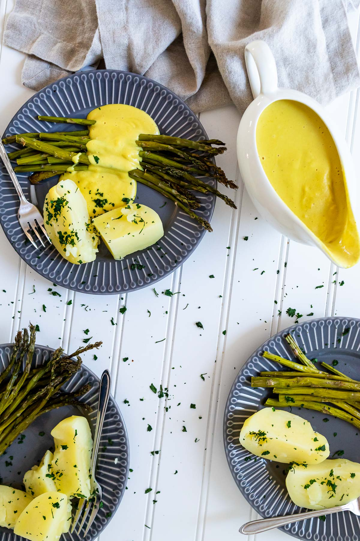 3 plates with asparagus, potatoes and vegan hollandaise sauce and one saucier with hollandaise