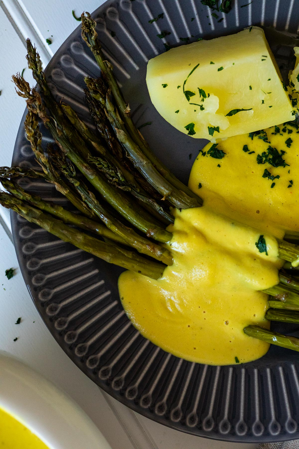Close up of one plate with asparagus, potatoes and hollandaise saucce