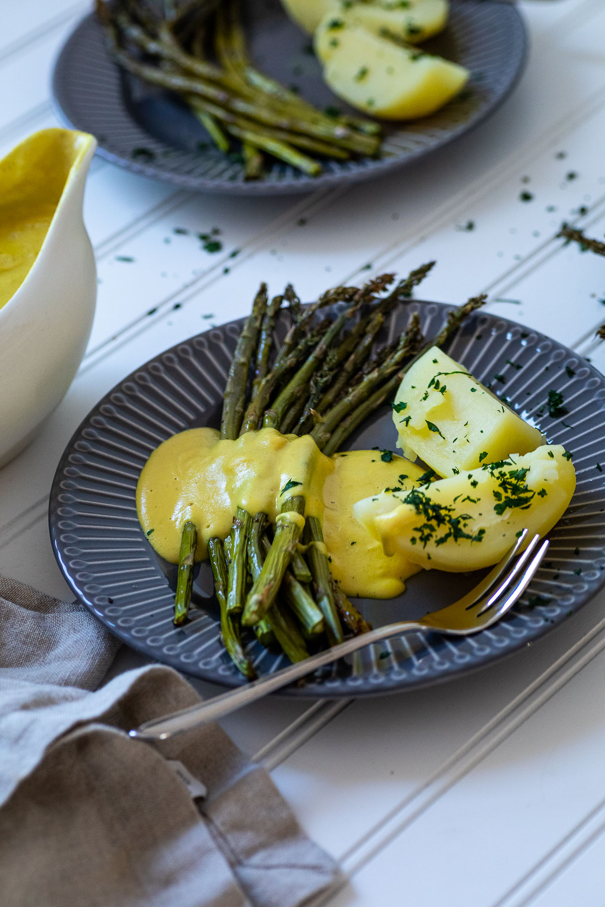 One Plate with Potatoes, Asparagus and dairy free hollandaise sauce with one plate in the background