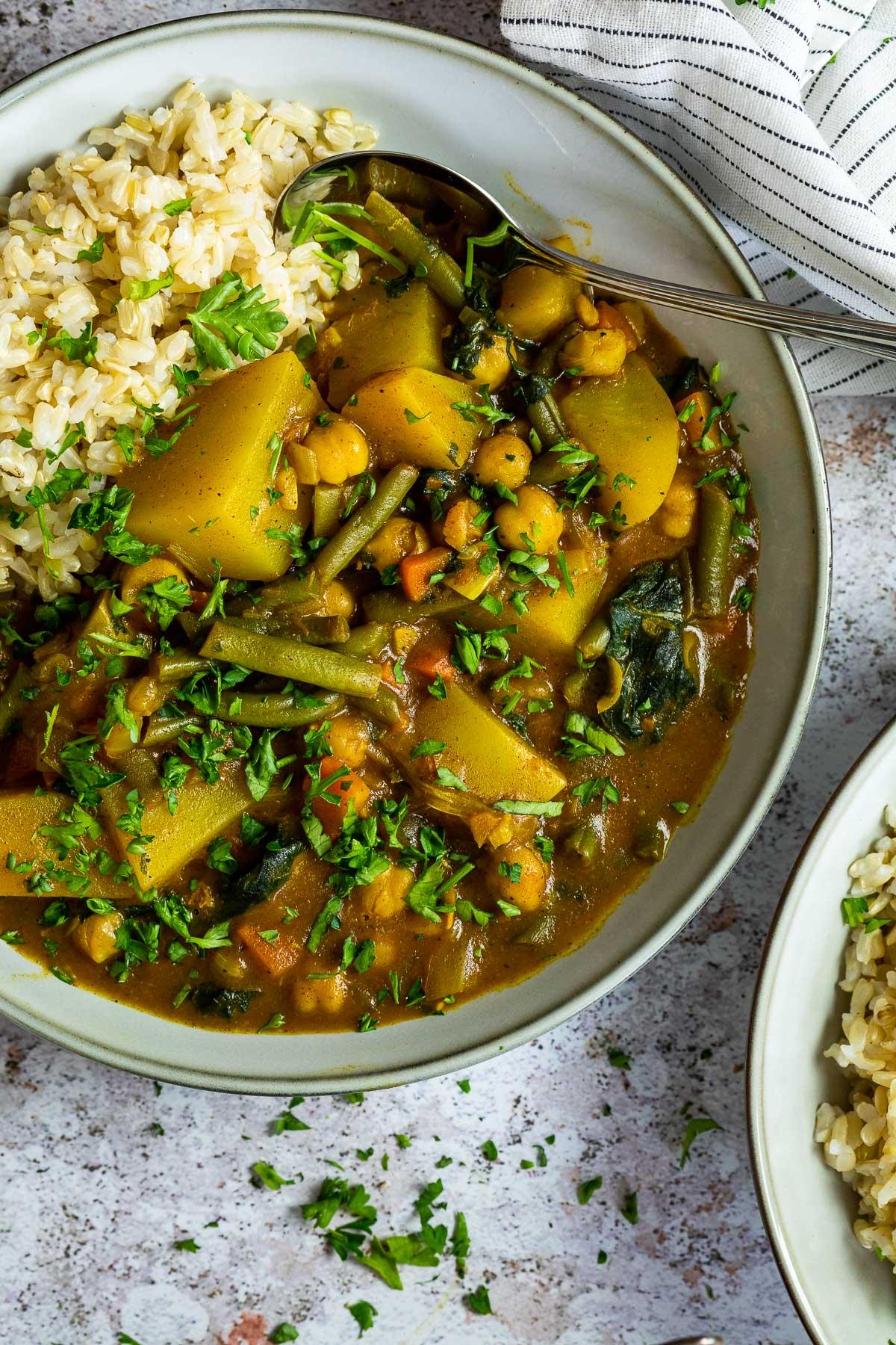 Schließen Sie oben von einem Teller mit Kartoffelcurry und Reis mit einem Tuch darüber