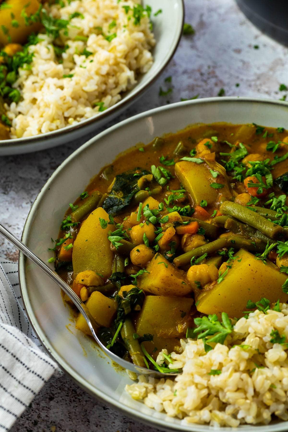 Ein Teller mit Kartoffelcurry und Reis und einem Löffel