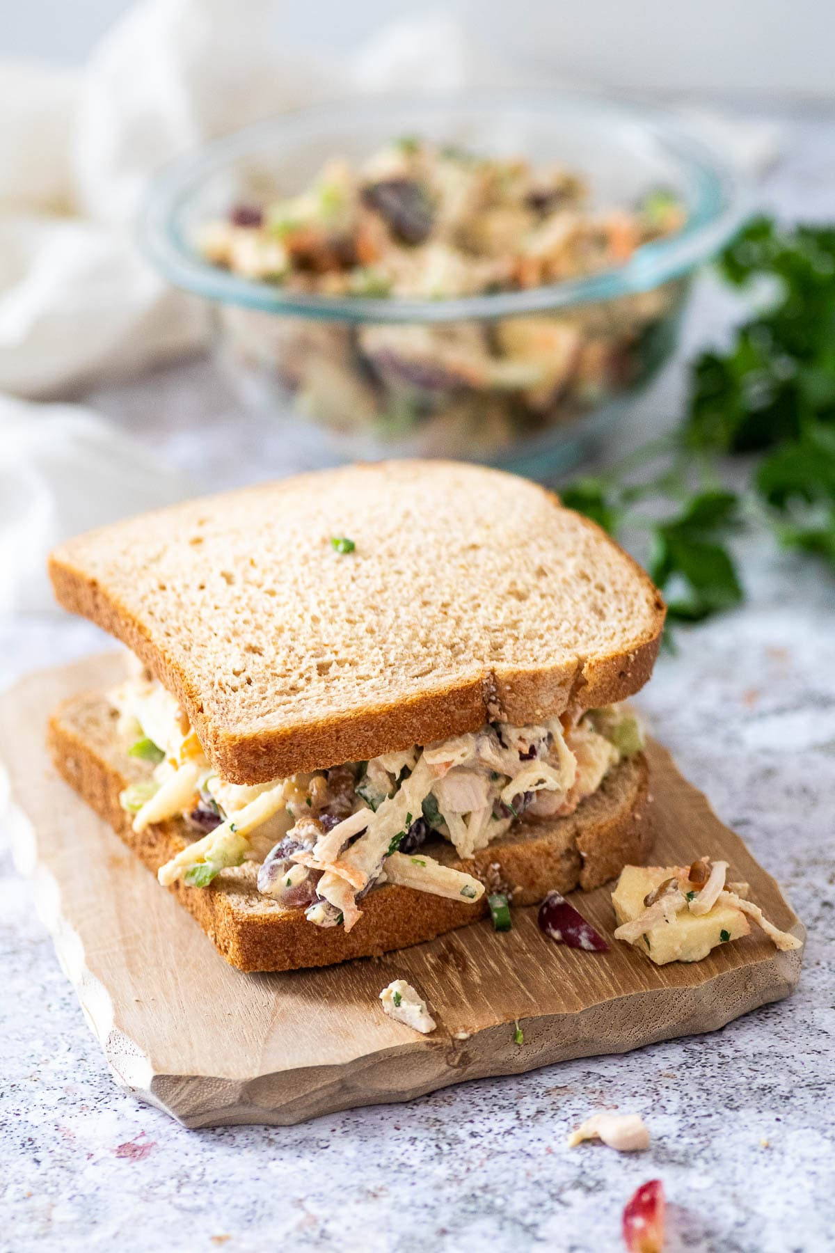 Chicken salad sandwich in the foreground and the bowl blurred in the background