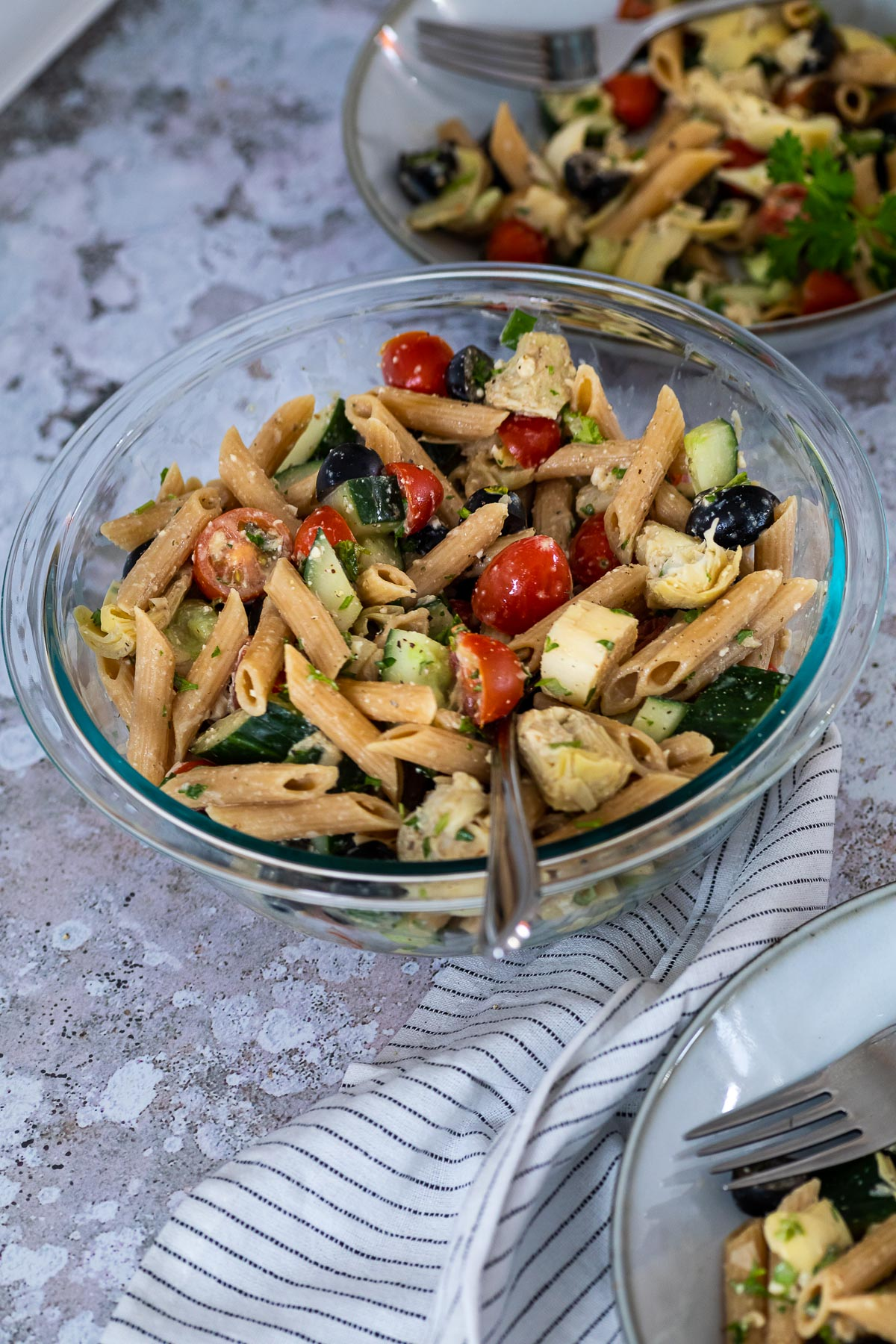 A bowl with vegan artichoke pasta salad and two plates in the background