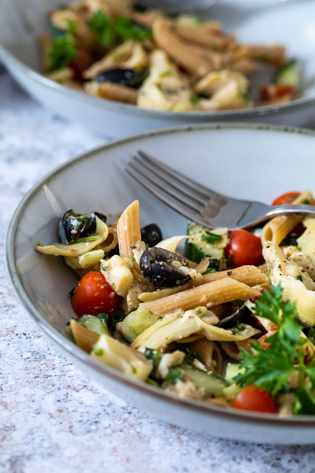 a plate with vegan artichoke pasta salad with a plate in the background