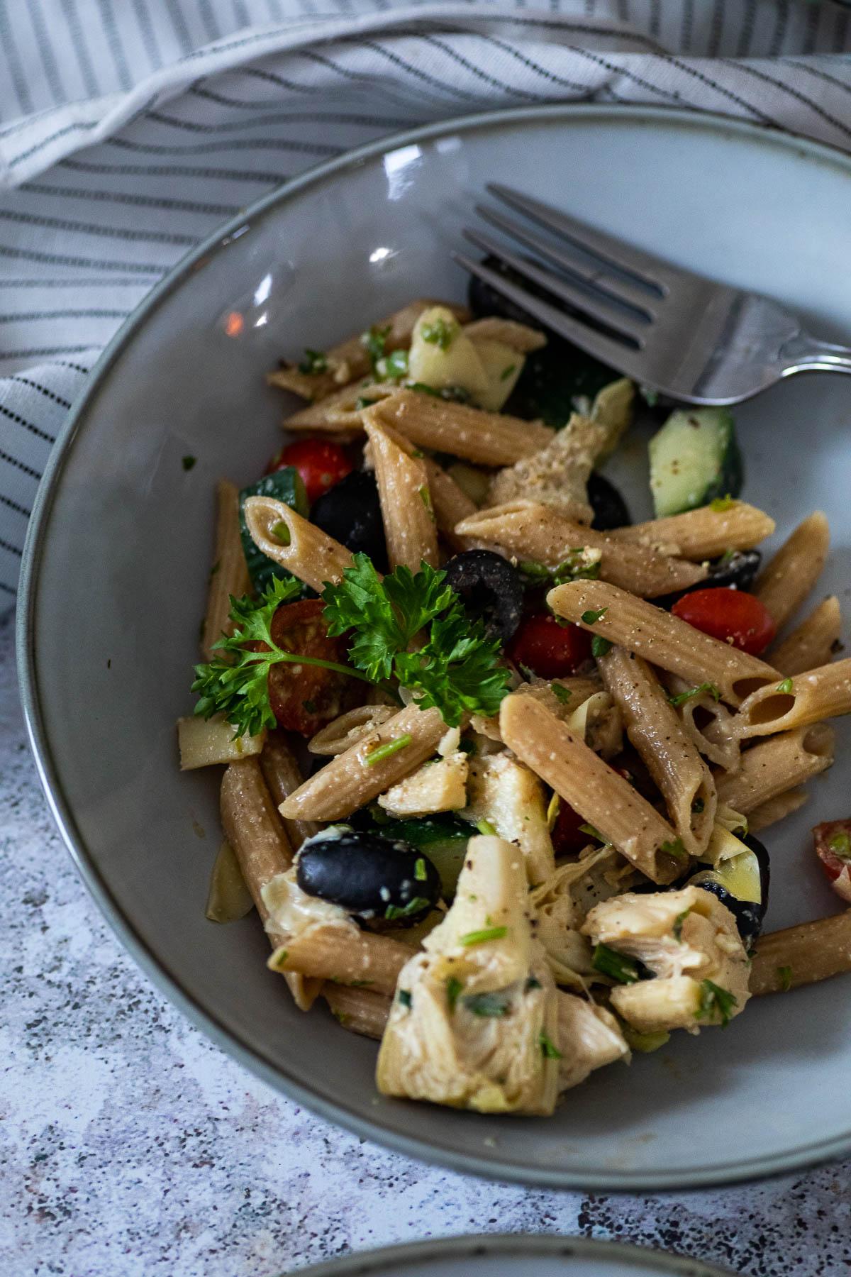 A plate with vegan artichoke pasta salad