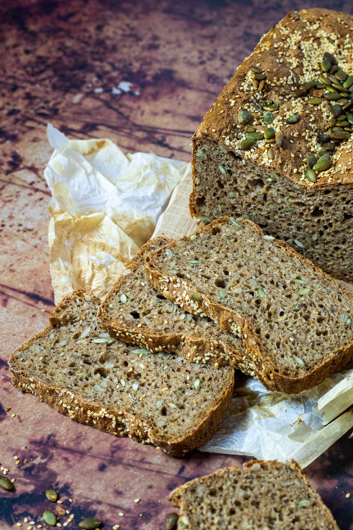 Artisan Spelt bread with 3 Slices in front of the half cutted spelt bread